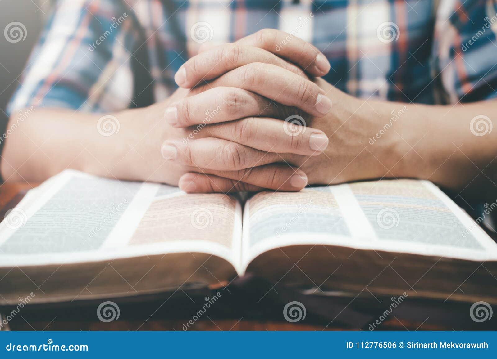 Équipez la prière, mains étreintes ensemble sur sa bible