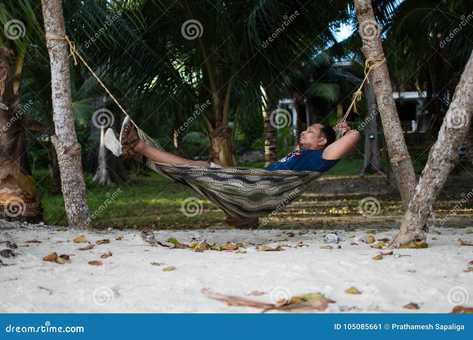 Équipez le sommeil sur un hamac ou un filet près sur une plage