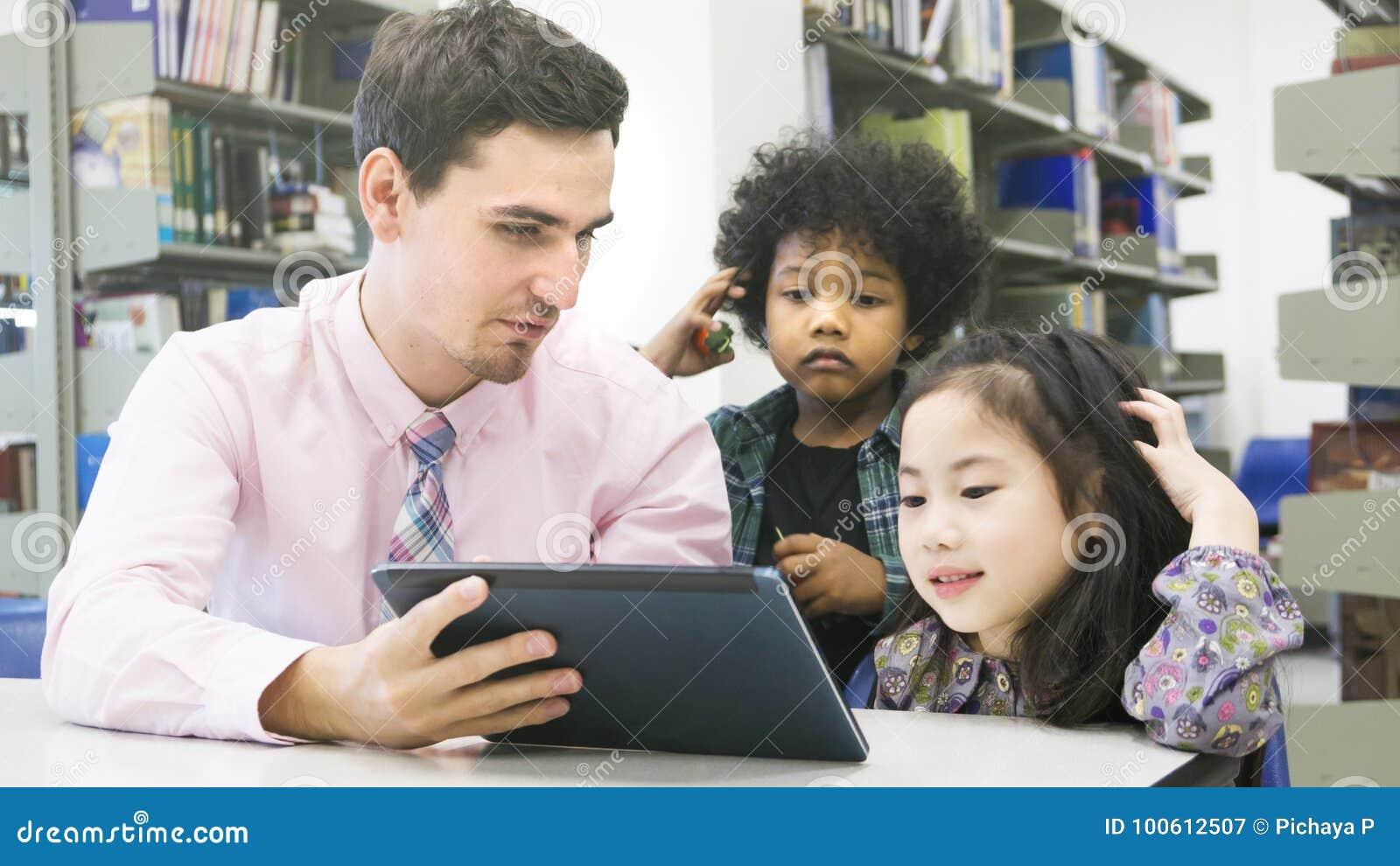 Équipez les étudiants de professeur et d enfant apprenant et regardant sur le devi de comprimé