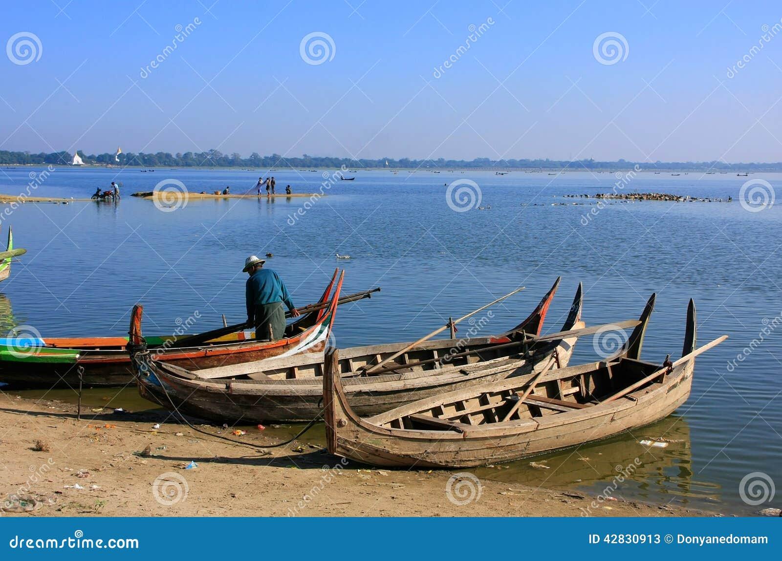 Équipez les bateaux en bois proches debout au lac, Amarapura, Myanmar