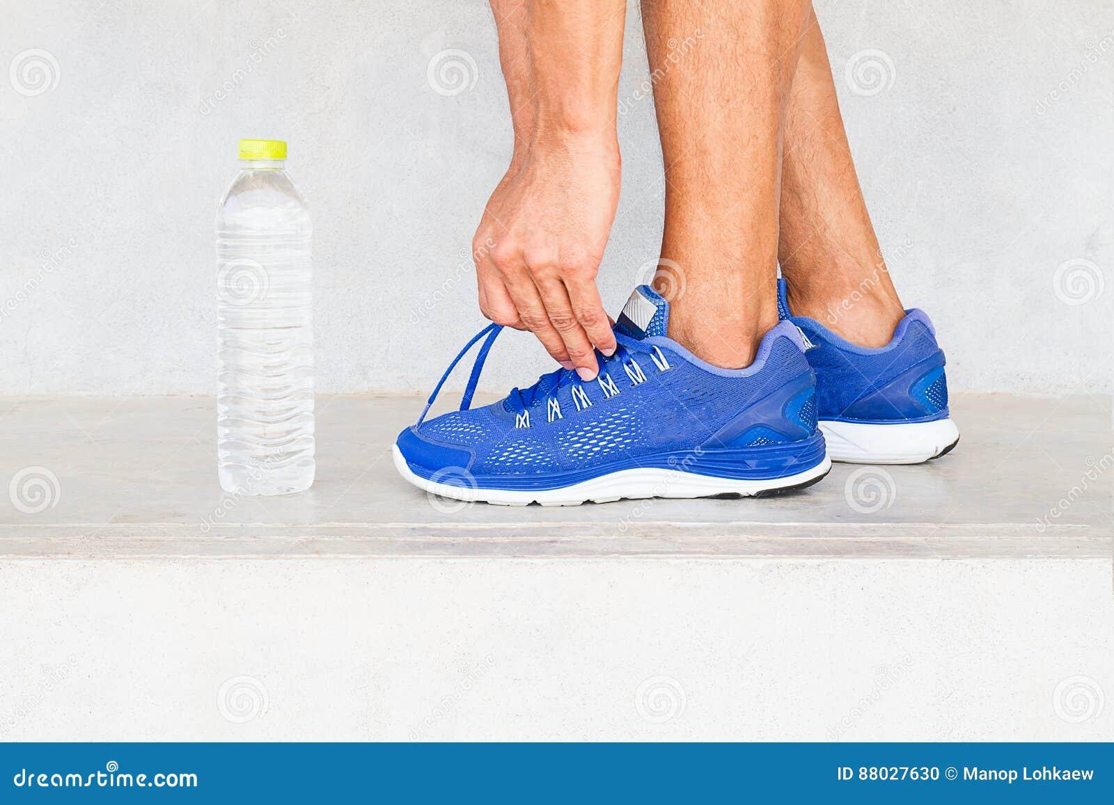 Équipez les chaussures de sport de laçage dans le gymnase avec la bouteille d eau, exercice de sport