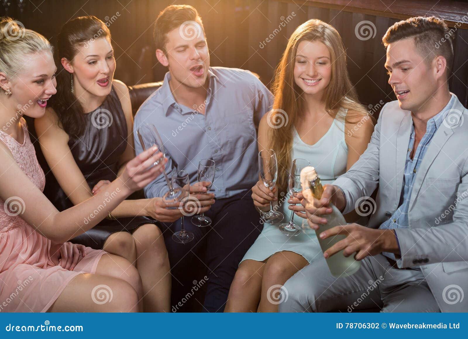 Équipez sauter une bouteille de champagne tandis que des amis l observant