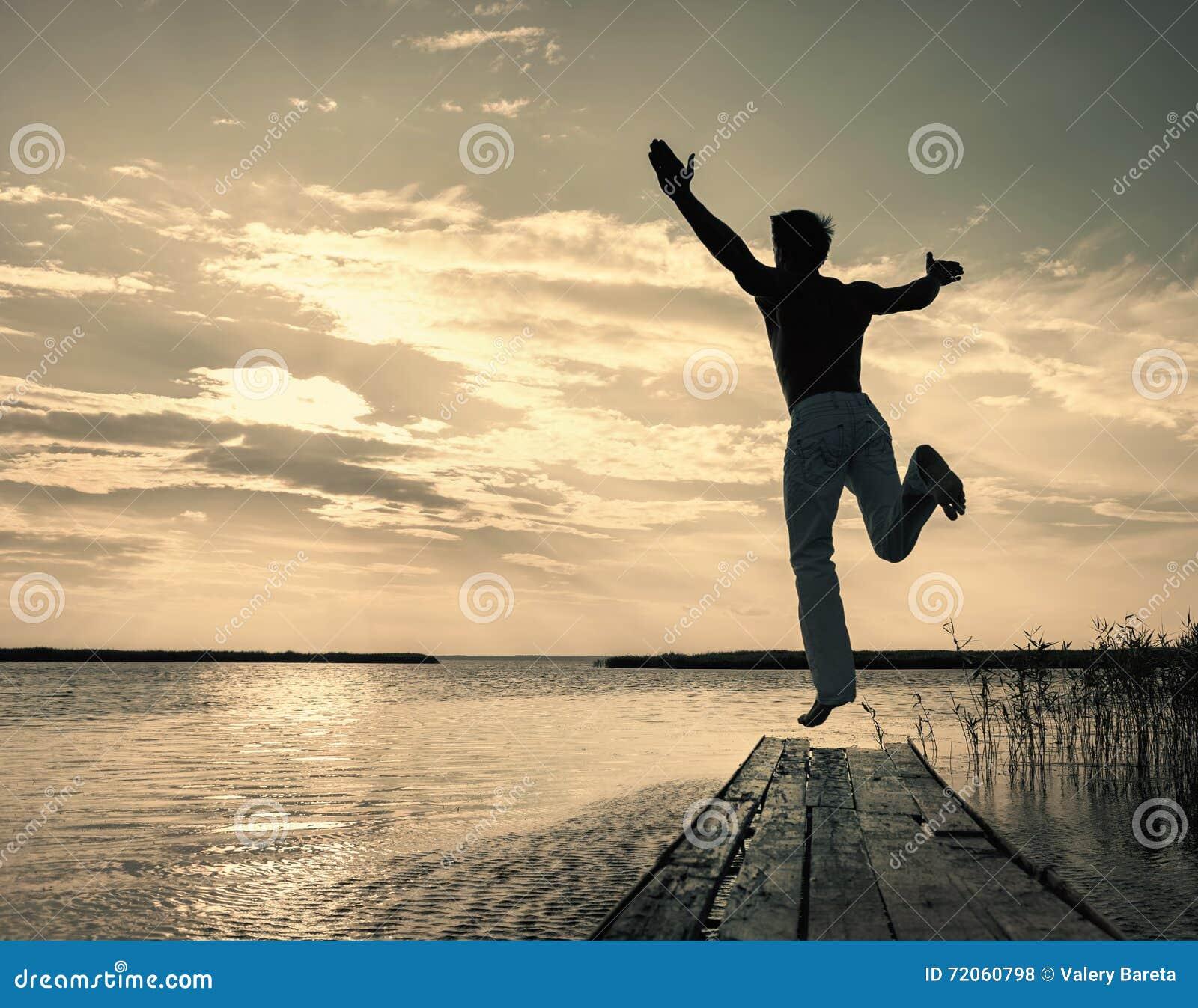 Équipez sauter vers le haut de outre de la petite jetée au coucher du soleil