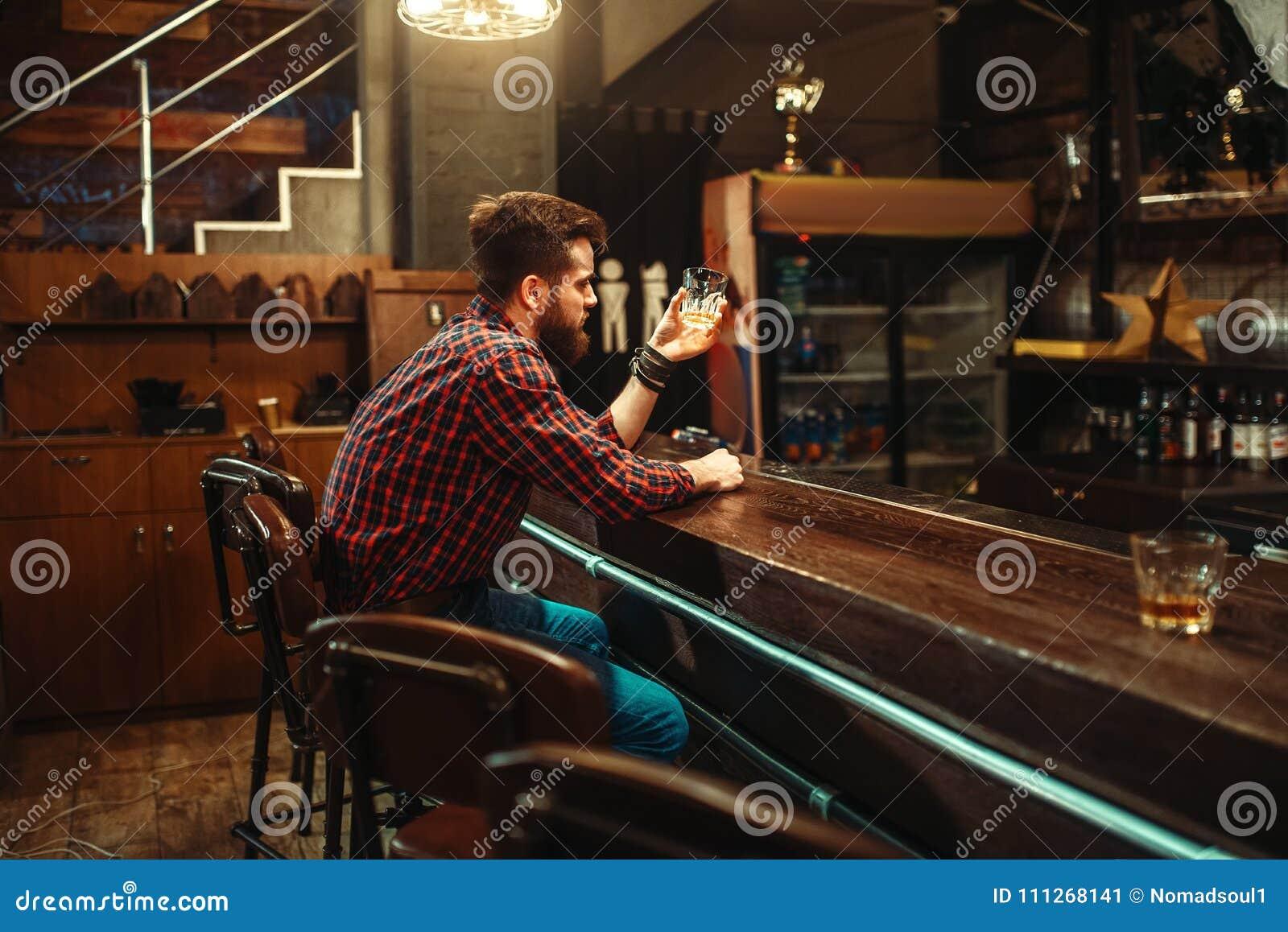 Équipez se reposer au compteur de barre et buvez l alcool