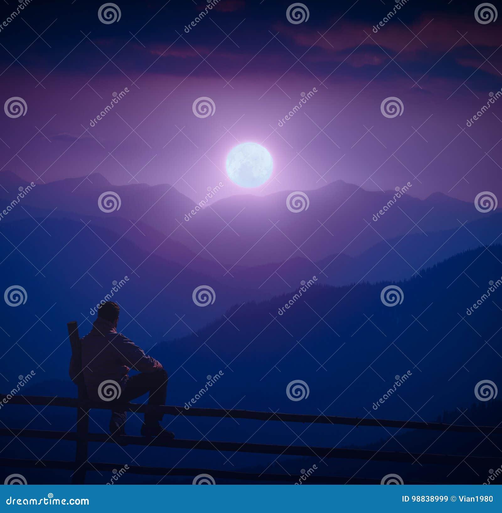 Équipez se reposer sur une barrière en bois et appréciez l augmentation de pleine lune