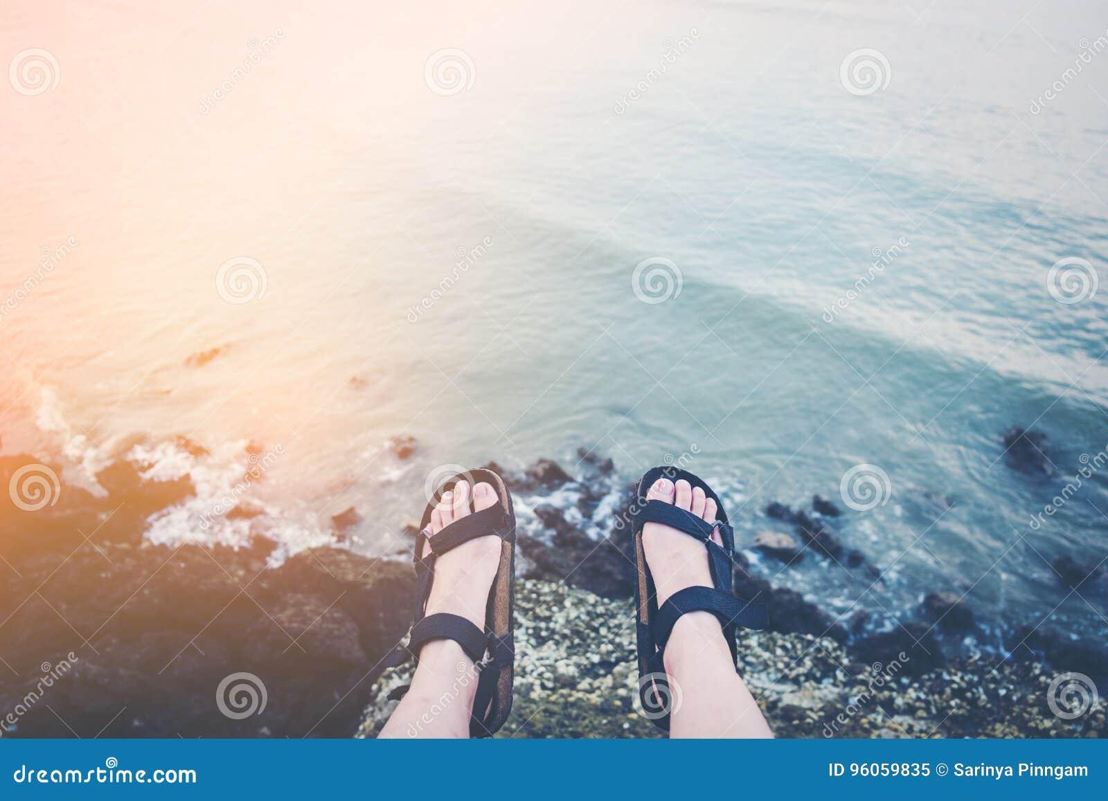 Équipez se reposer sur une haute falaise au-dessus d océan