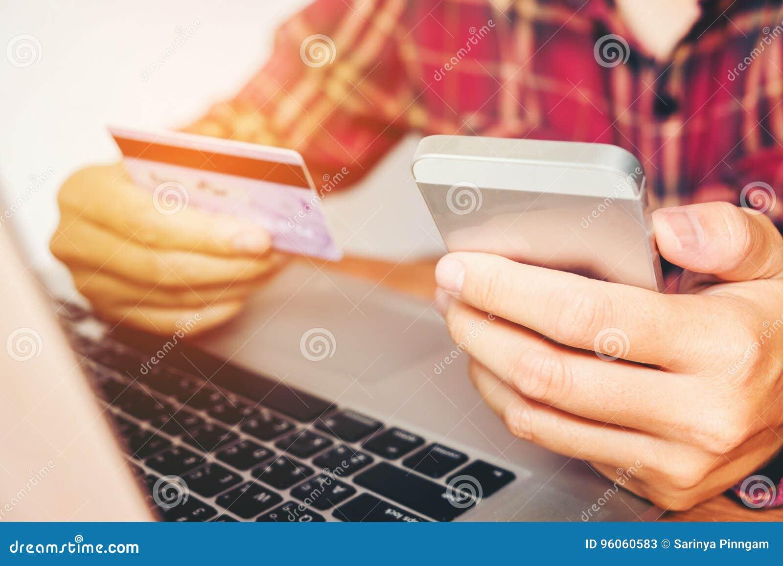 Équipez tenir la carte de crédit et à l aide du téléphone portable tenant la carte de crédit avec faire des emplettes en ligne