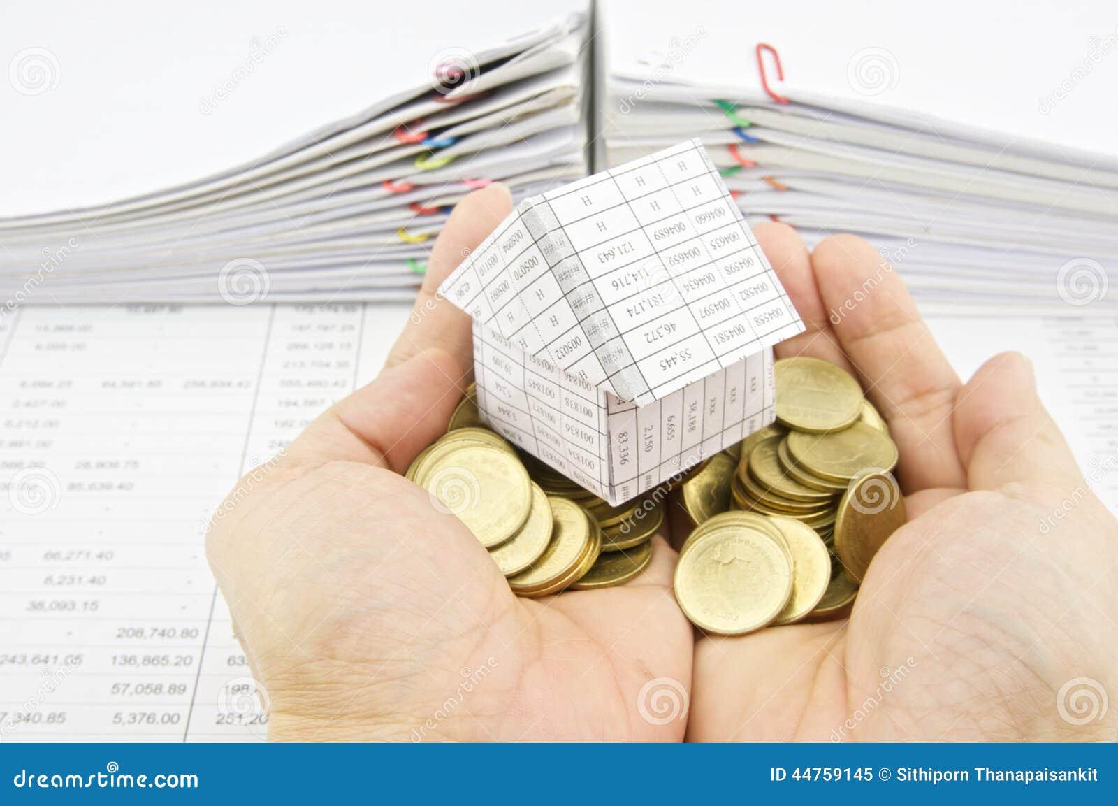 Équipez tenir la maison sur des pièces d'or de pile au-dessus de