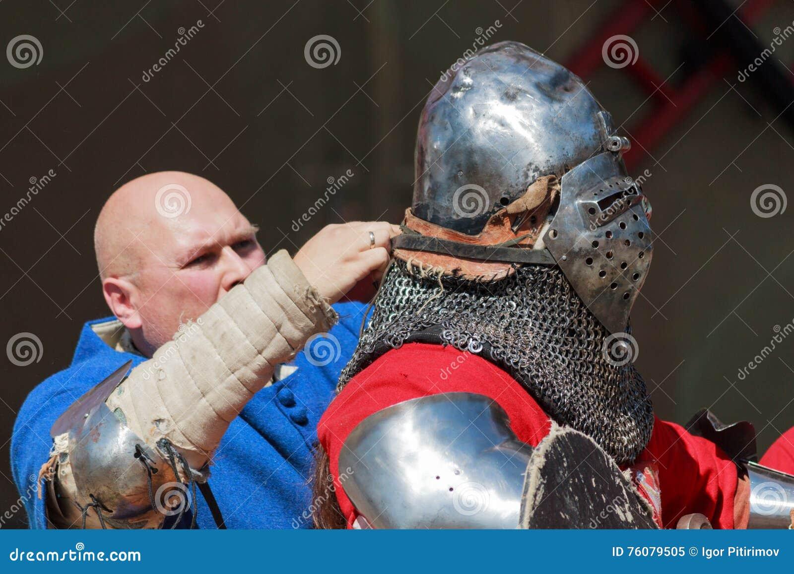 Équipier aidant à mettre dessus le chevalier les armures avant bataille