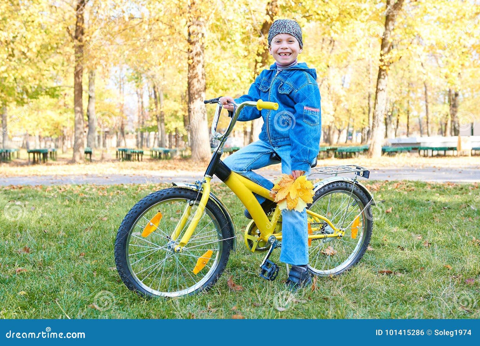 Équitation de garçon sur la bicyclette en parc d automne, jour ensoleillé lumineux, feuilles tombées sur le fond
