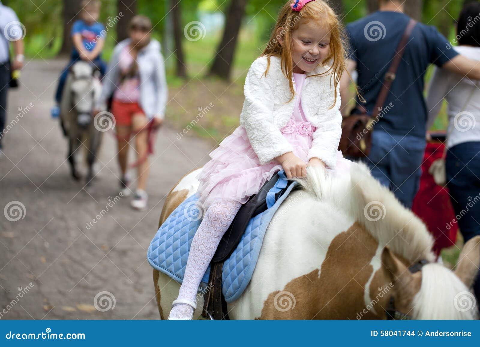 Équitation de petite fille sur un poney en parc de ville