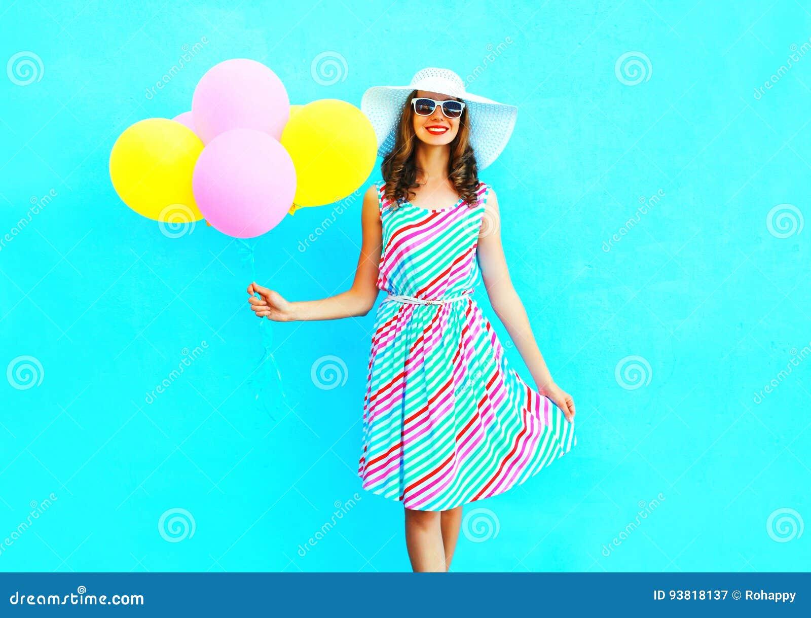 Été ! La jeune femme de sourire heureuse de mode tient les ballons colorés d un air