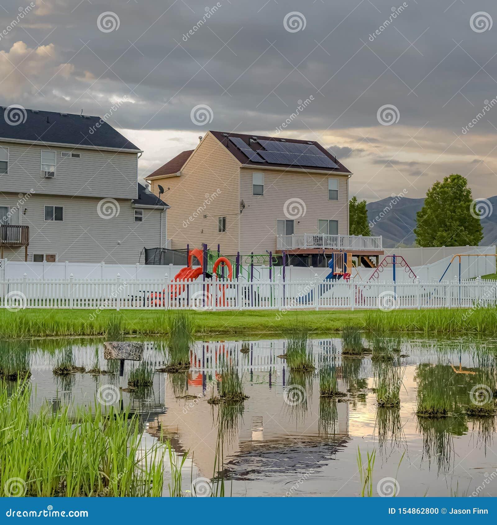 Étang herbeux brillant de place avec la réflexion des maisons ciel nuageux et barrière de terrain de jeu