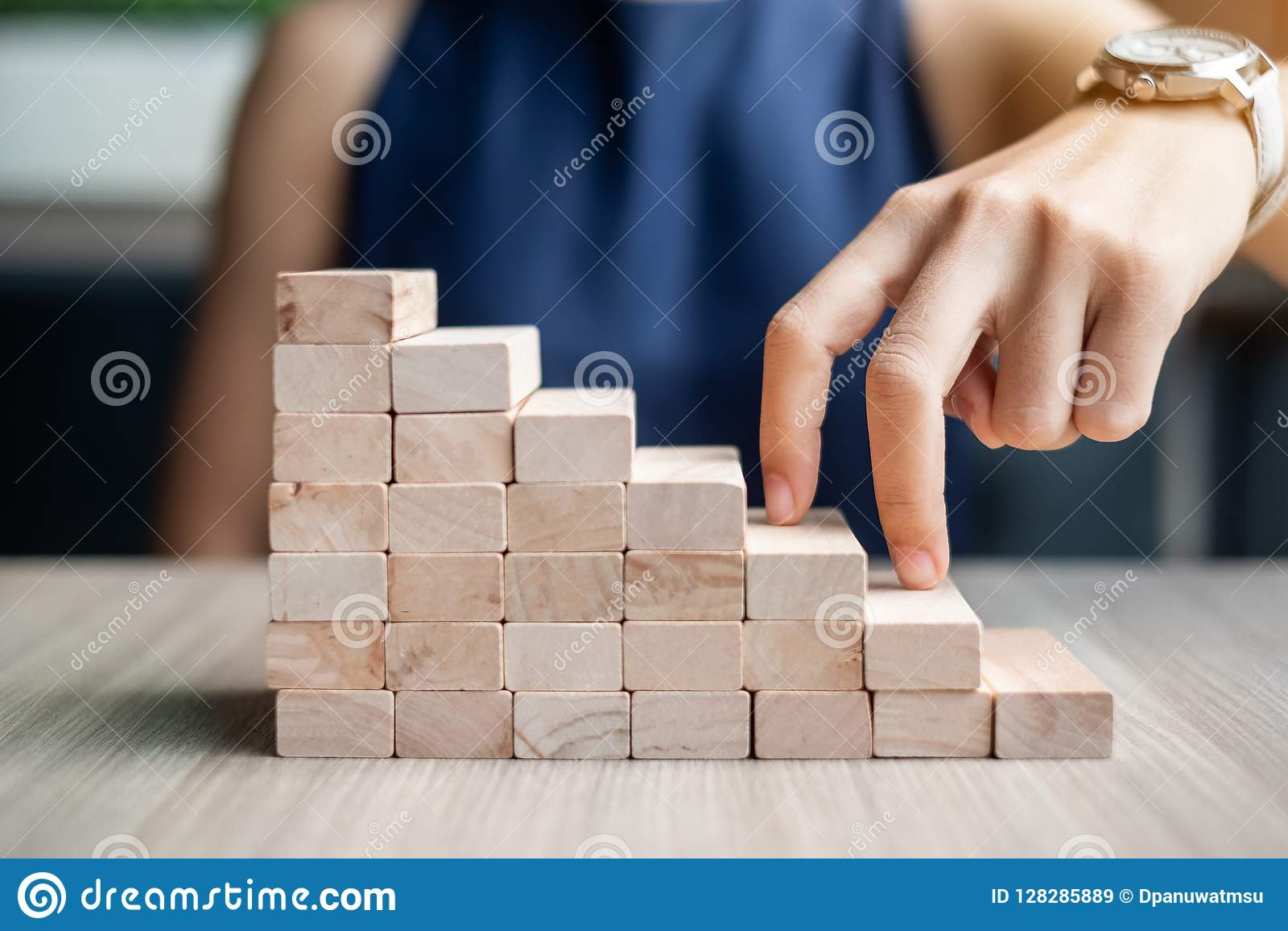 Étape de doigt de femme d affaires sur le bâtiment en bois de bloc