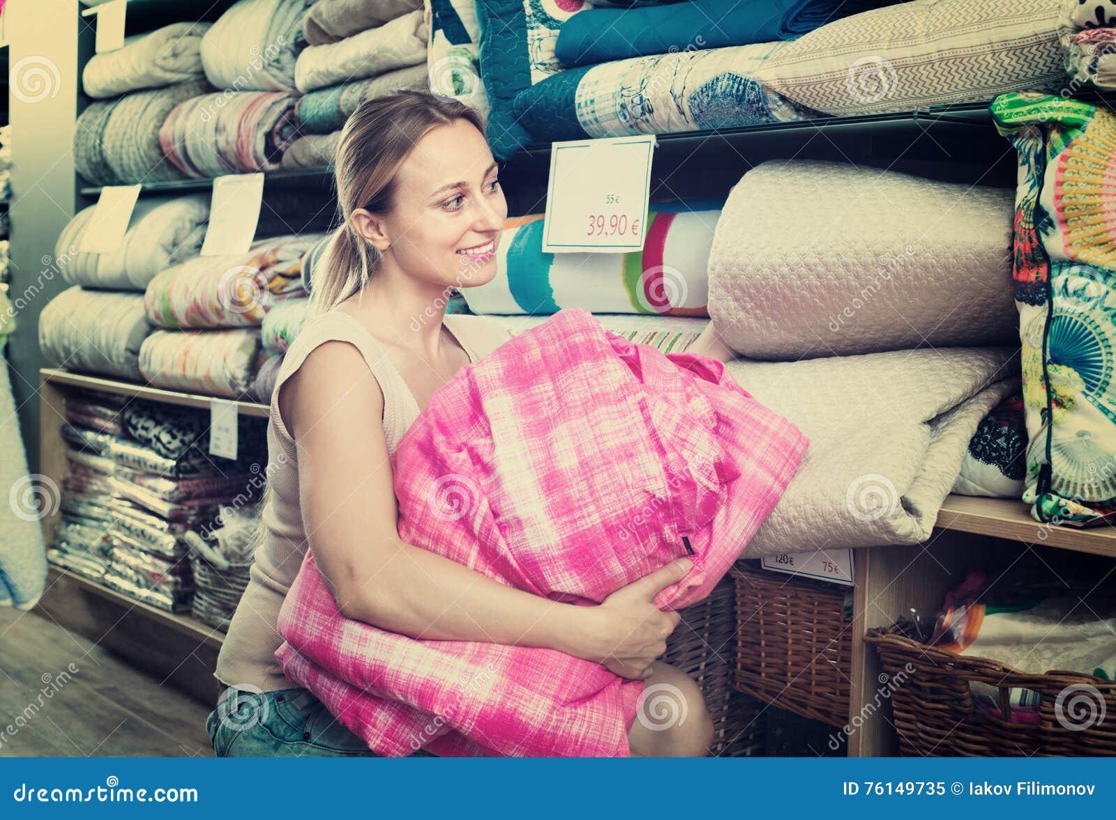 Étendre de achat de lit de youngwoman dans le magasin de textile