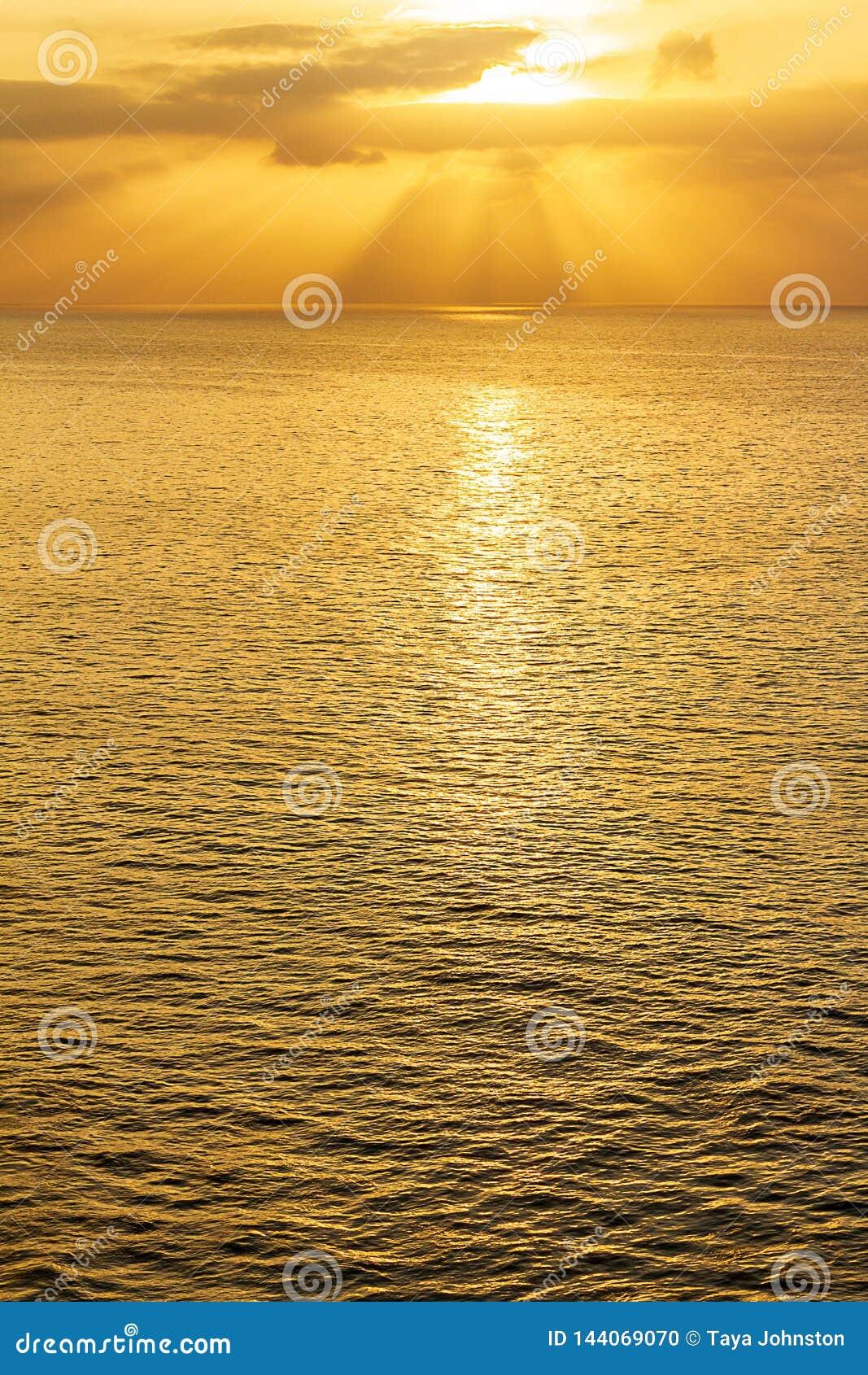 Étendue d océan au lever de soleil avec des rayons de soleil et des nuages