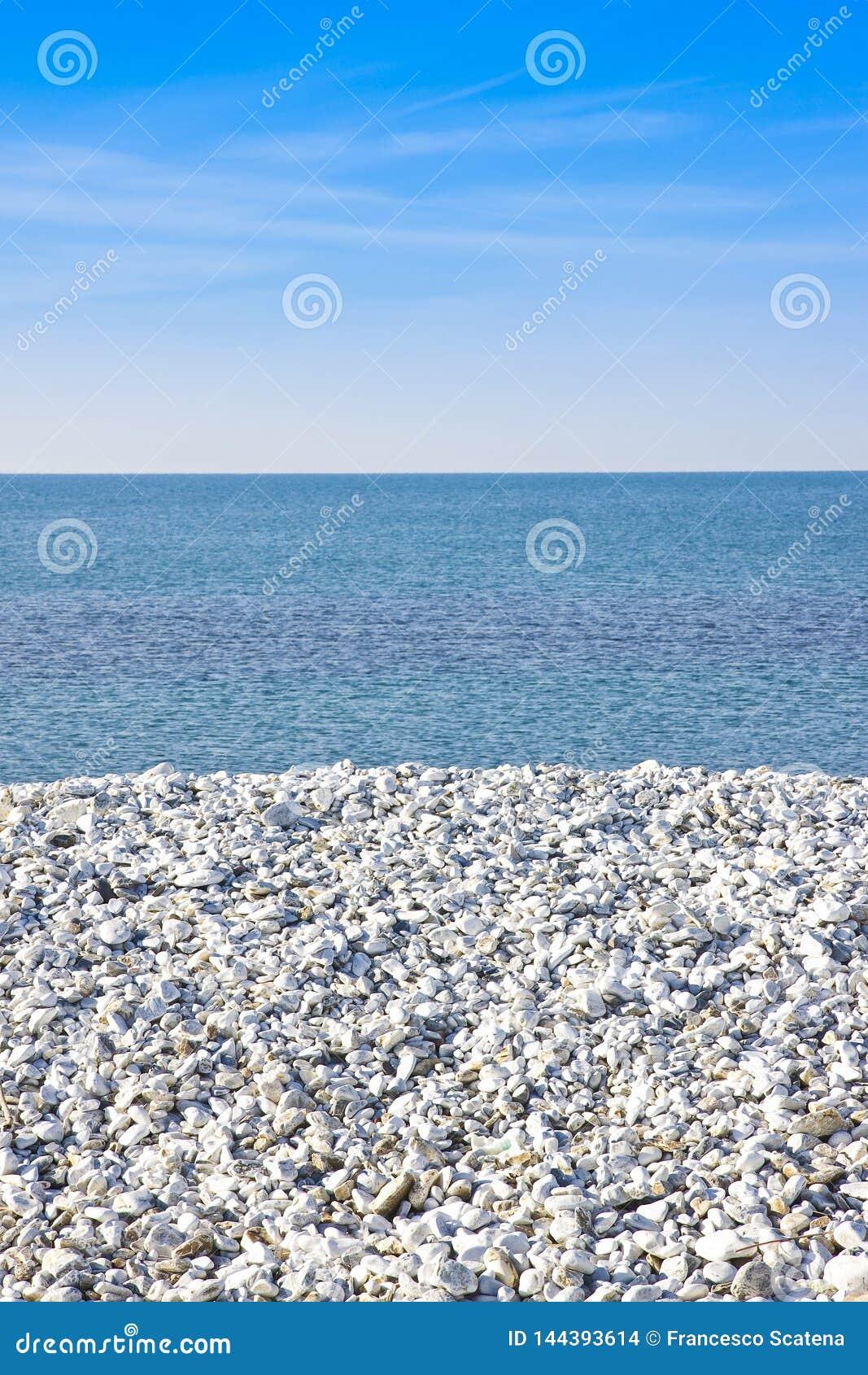 Étendue du gravier blanc sur la côte avec la mer calme sur le backgr