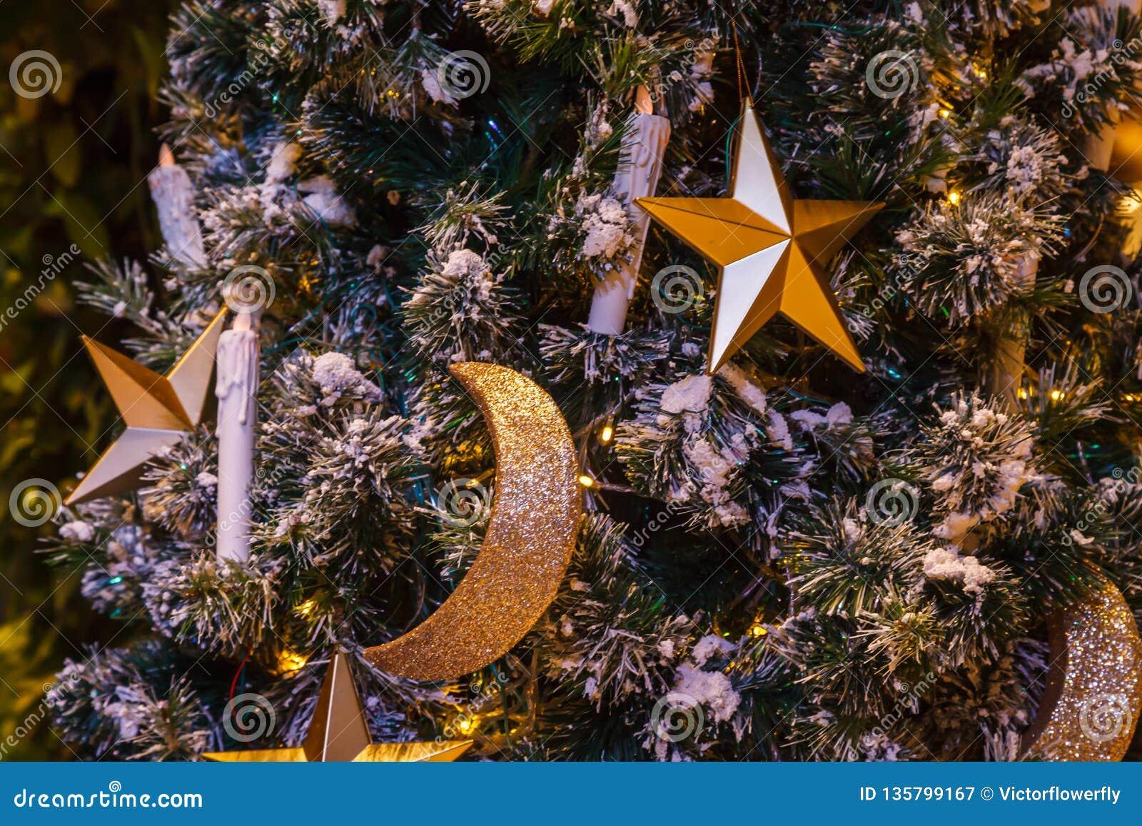 Étoile d or, croissant de lune et fond éclatants accrochants de babioles de boule avec l arbre de Noël neigeux décoré d hiver dan