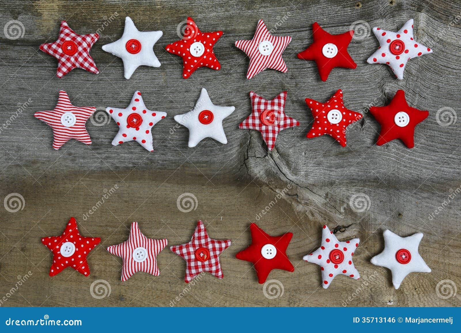 Étoiles rouges et blanches de décoration de Joyeux Noël de tissu sur  rustique