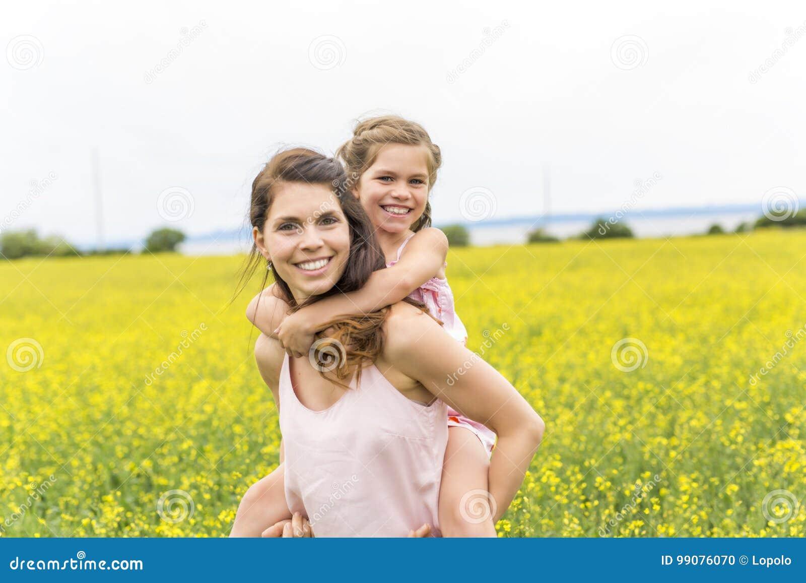 Étreinte heureuse de fille de mère et d enfant de famille sur les fleurs jaunes sur la nature en été