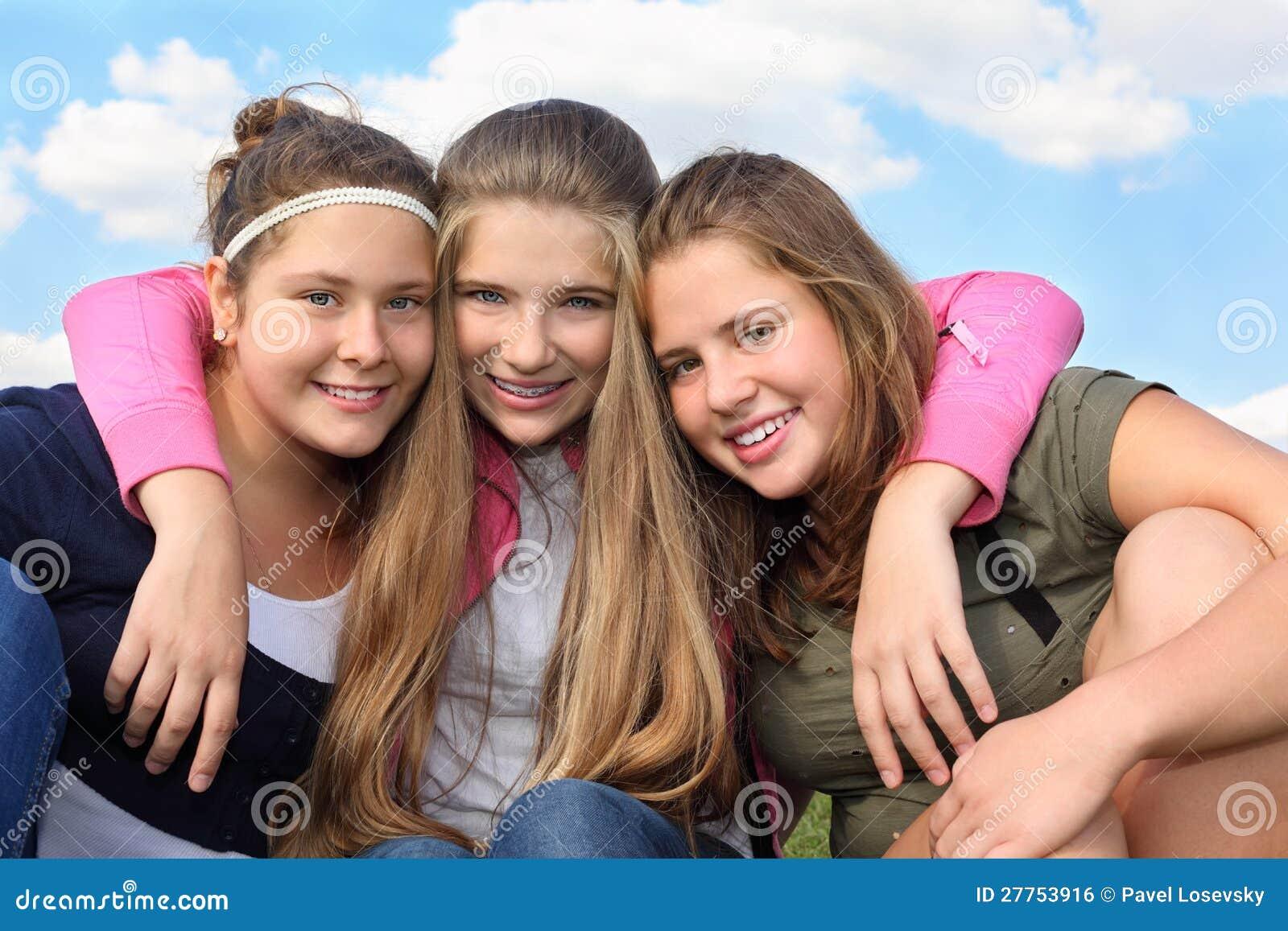 Étreinte heureuse de trois filles au fond du ciel