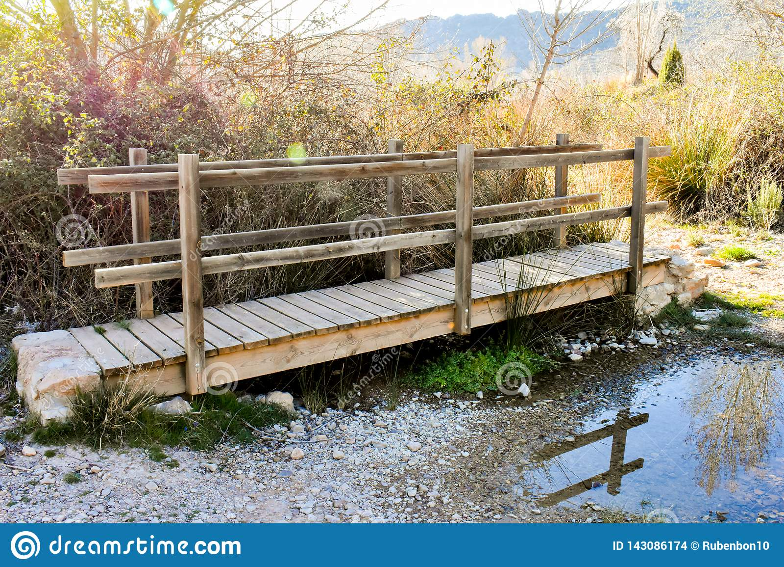 étroit d un pont en bois sur une abondance de rivière des herbes et des précipitations dans la lumière ensoleillée du lever de so