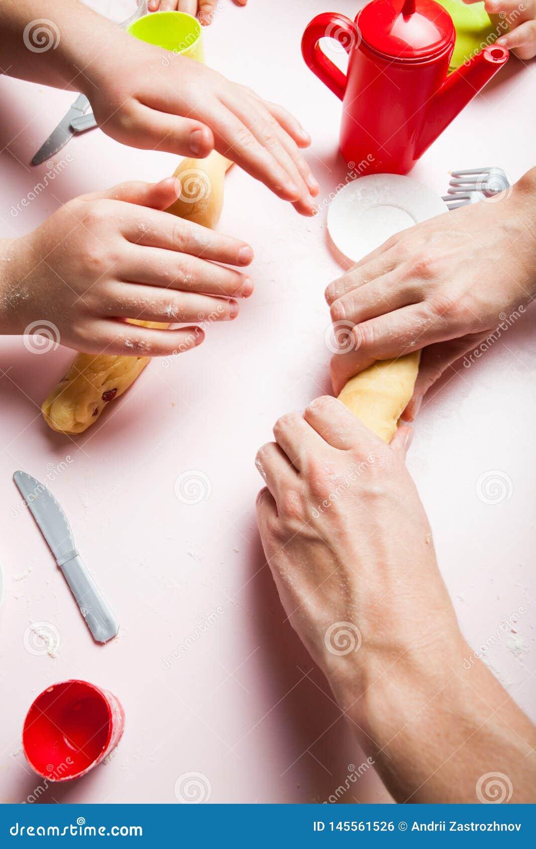 Étroitement, la fille de mère et d enfant préparant la pâte, font des biscuits cuire au four Les mains de l enfant faisant des bi