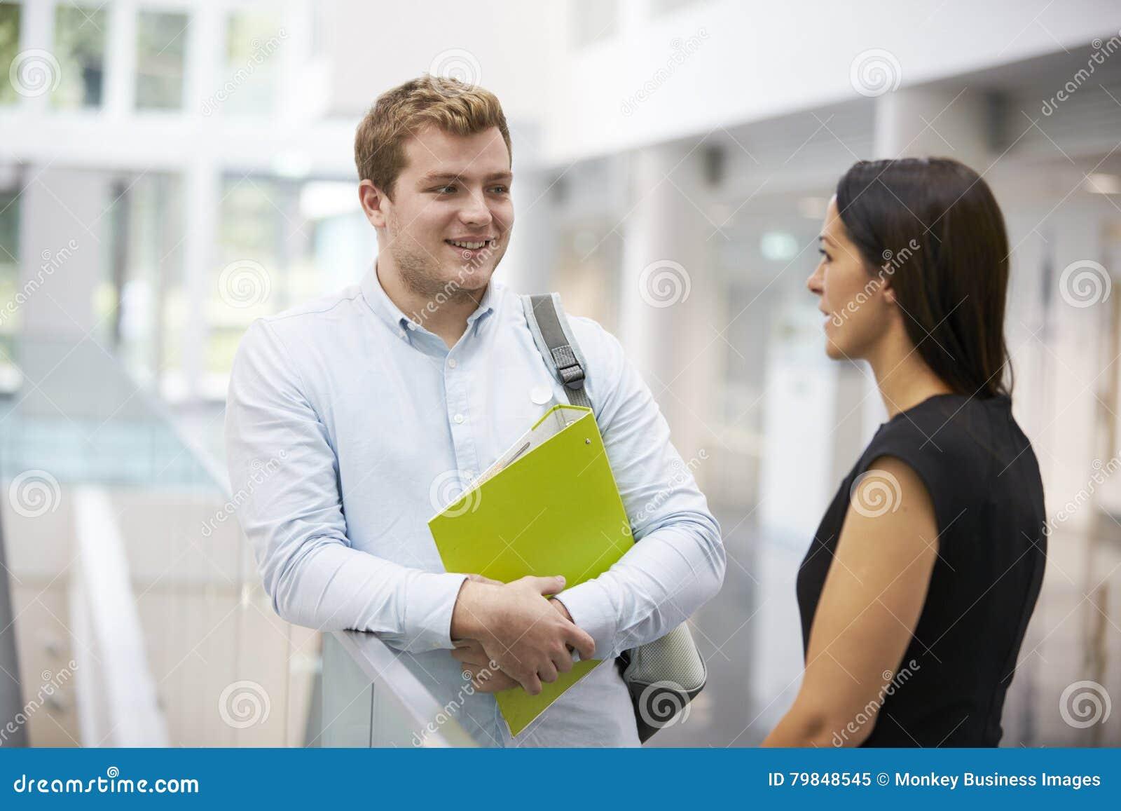 Étudiant adulte et professeur parlant dans le foyer d université