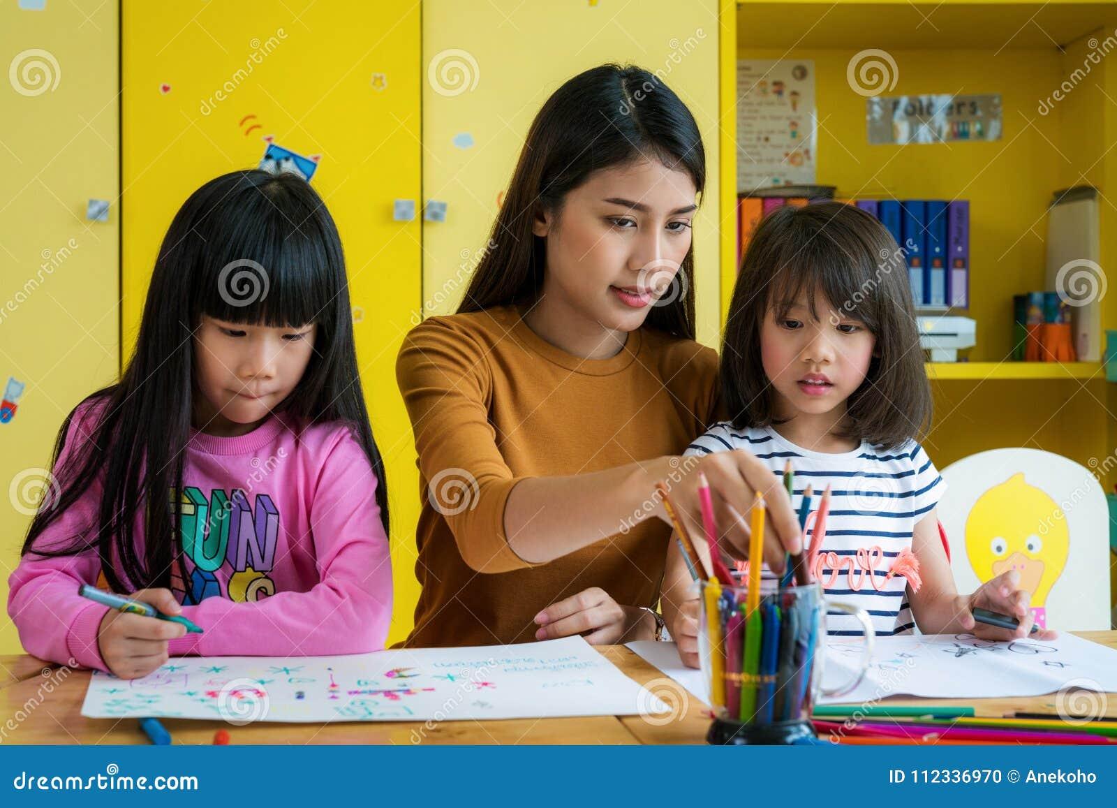 Étudiant asiatique de professeur et d école maternelle dans la classe d art
