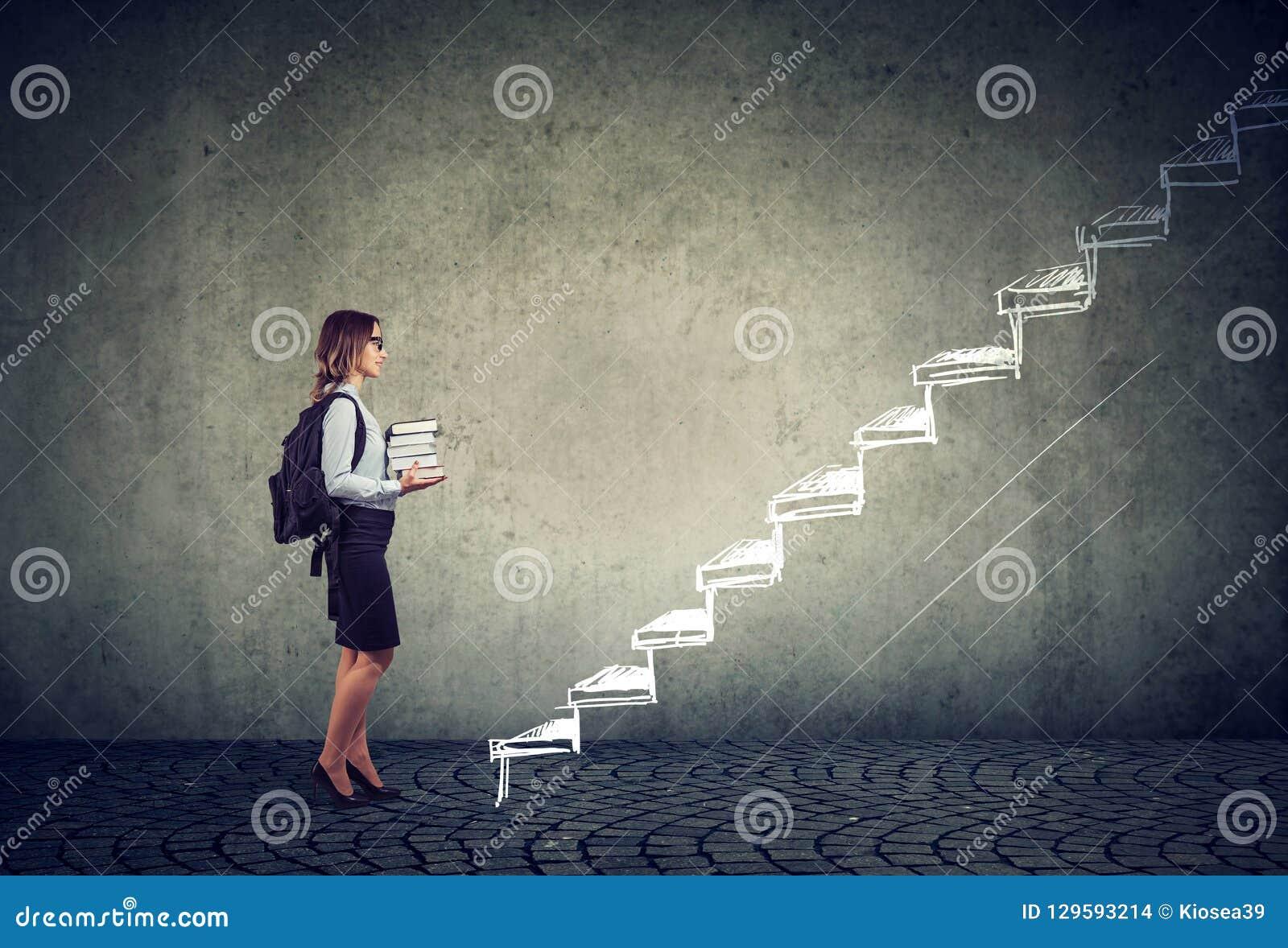 Étudiant avec des livres se tenant sur les escaliers de l éducation menant au succès