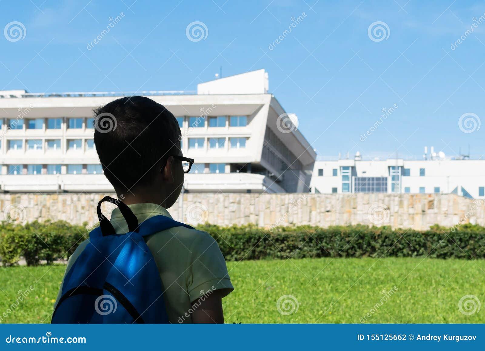 Étudiant avec un sac à dos sur ses regards arrières au bâtiment scolaire