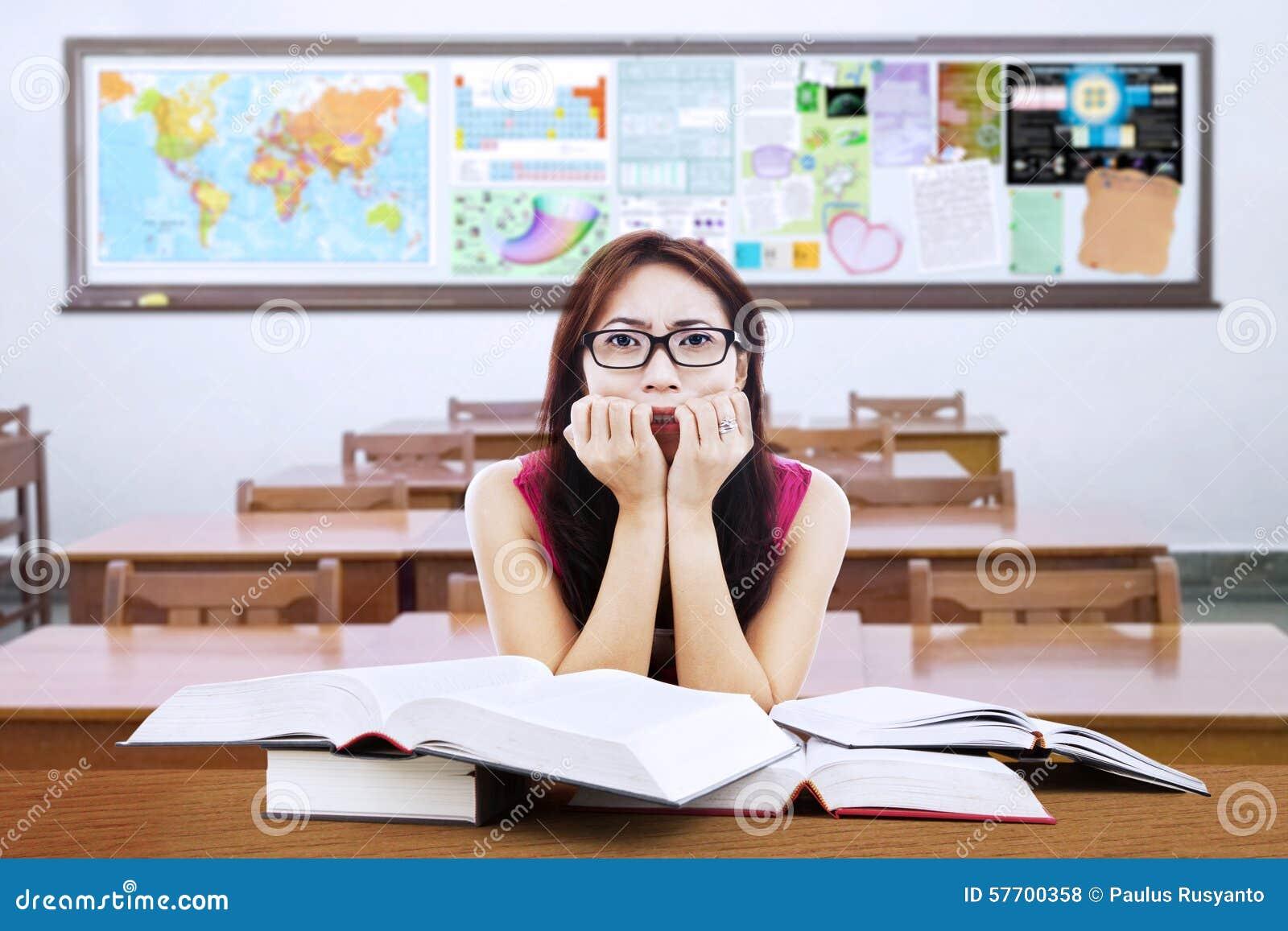 Étudiant confus de brune avec des livres dans la classe