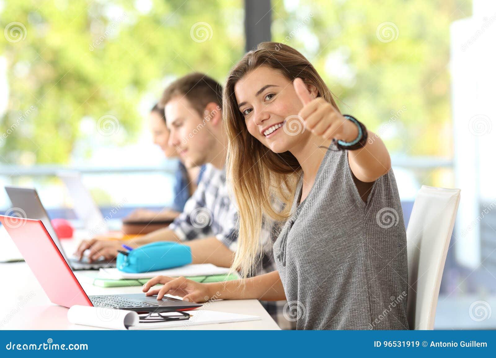 Étudiant heureux avec des pouces dans une salle de classe