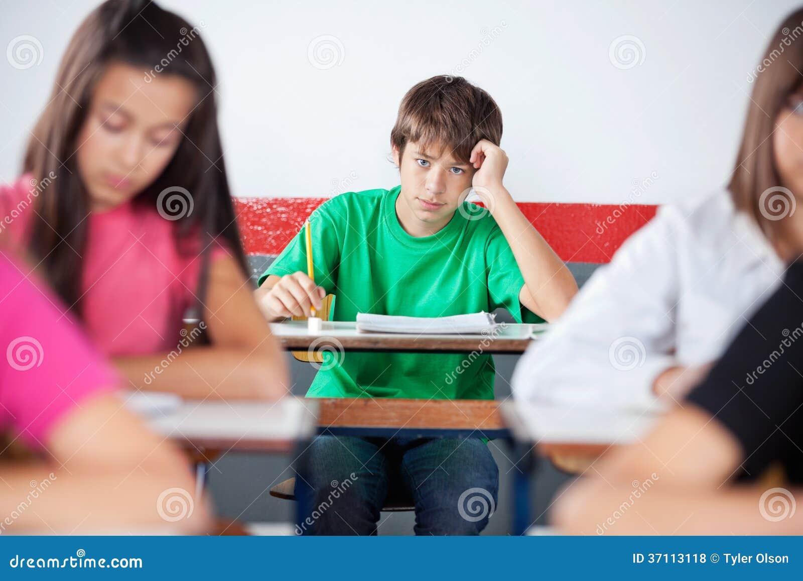 Étudiant masculin adolescent Leaning On Desk à la salle de classe