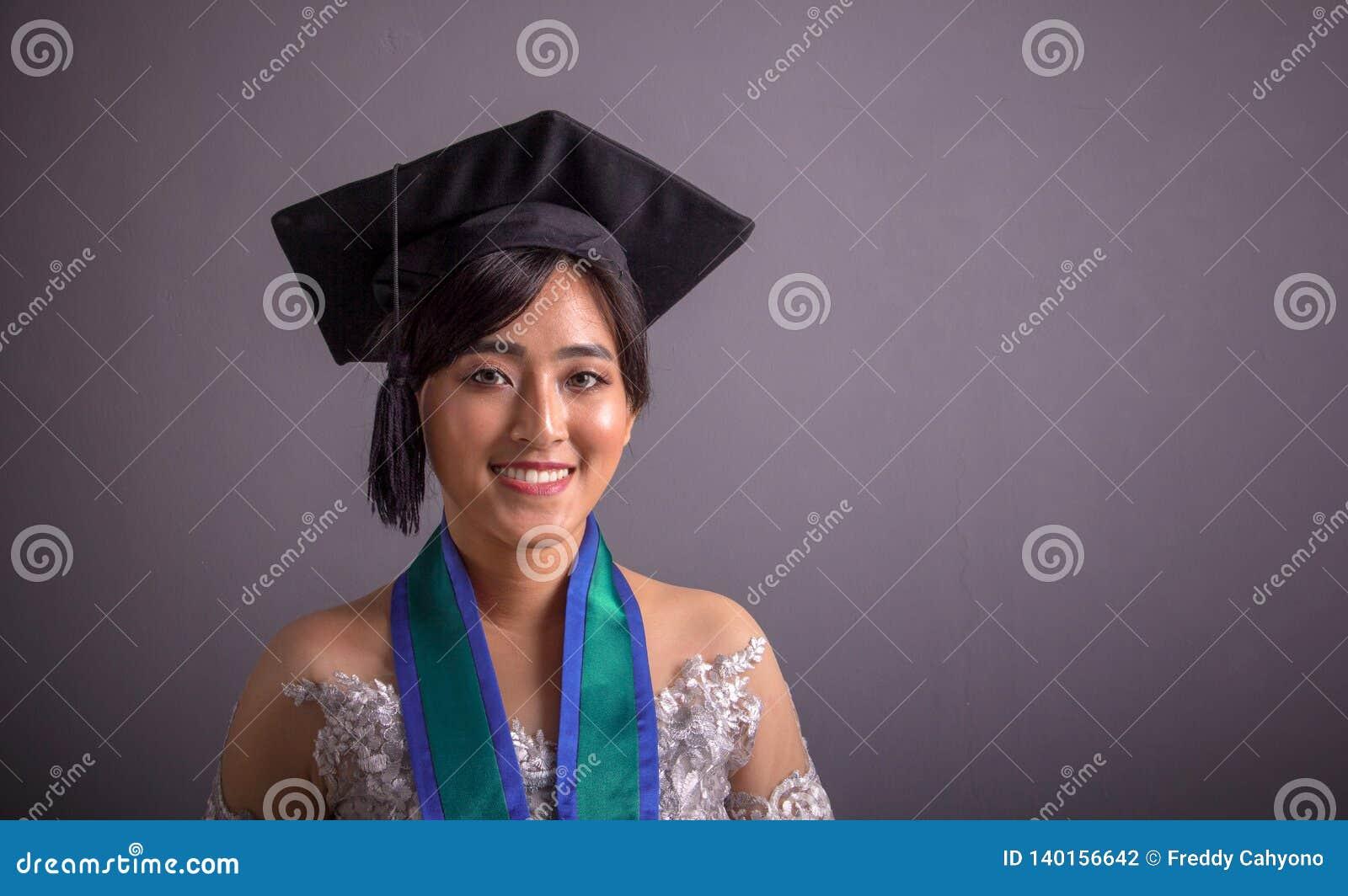 Étudiant universitaire féminin en portrait de plan rapproché de chapeau d obtention du diplôme au-dessus de gris