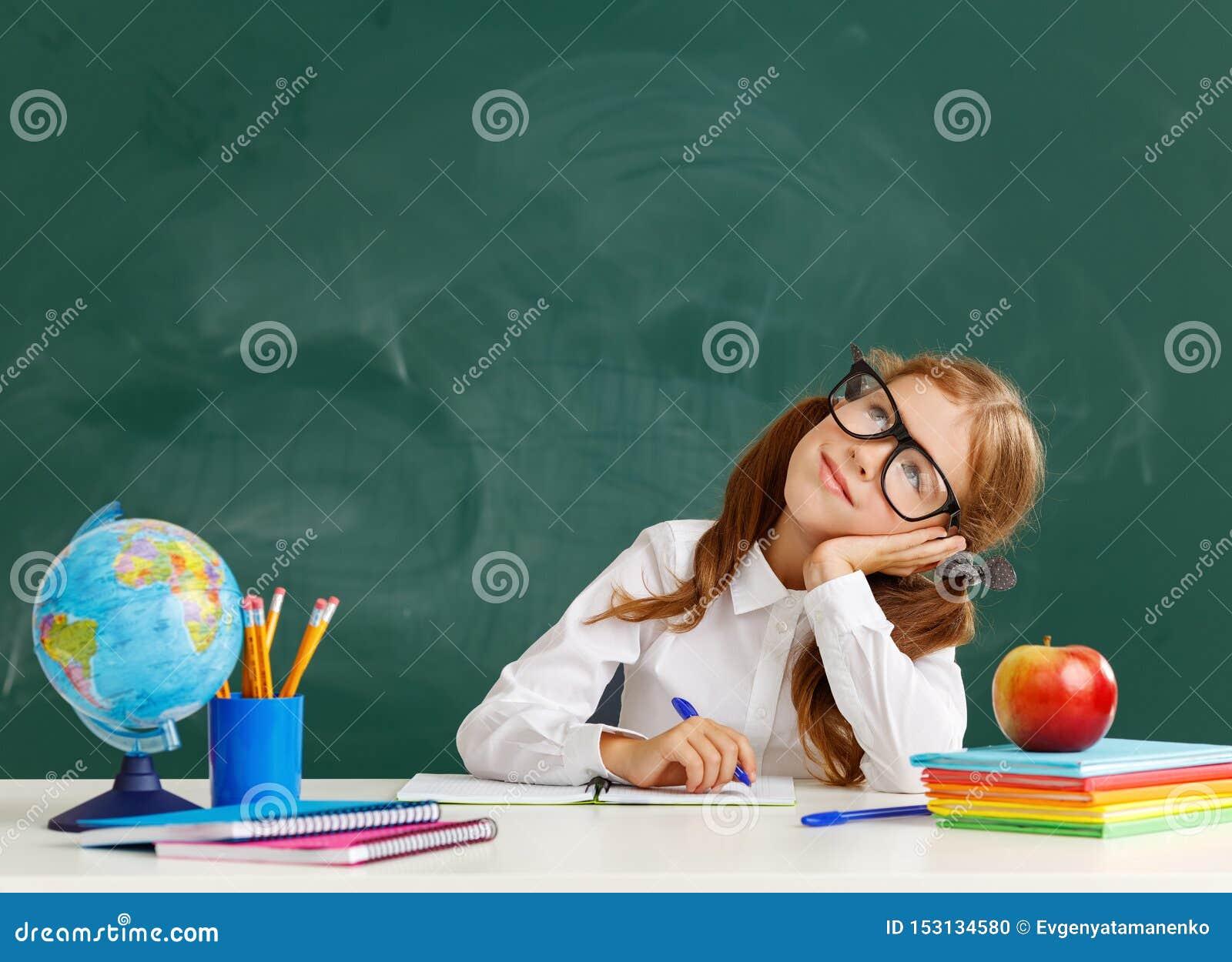 Étudiante d écolière d enfant au sujet de tableau noir d école