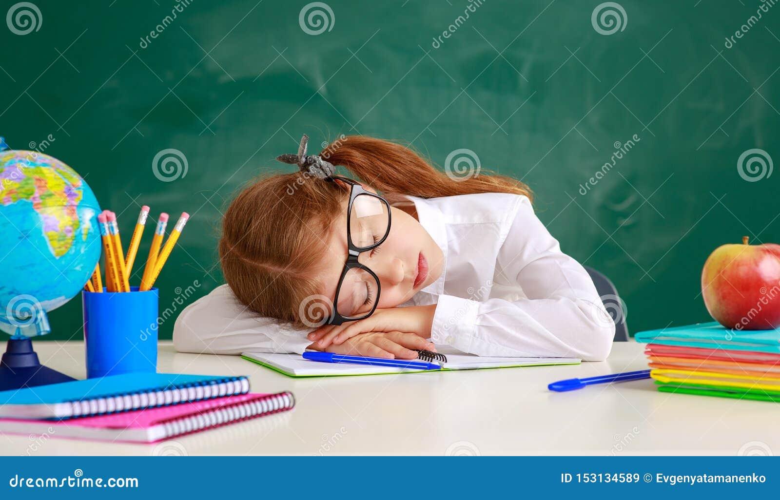 Étudiante d écolière d enfant fatiguée, endormi au sujet du tableau noir d école