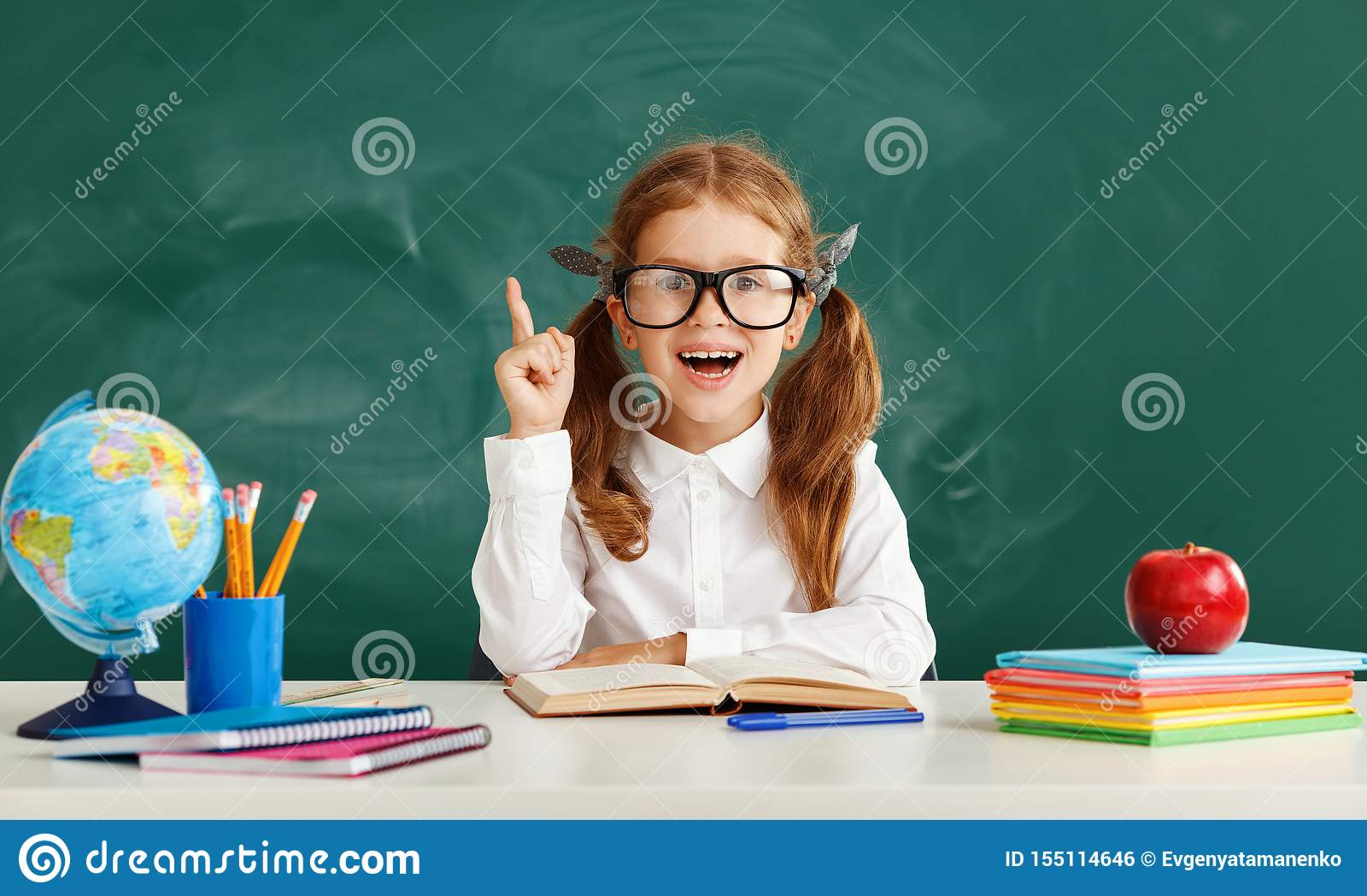 Étudiante drôle d écolière d enfant au sujet de tableau noir d école