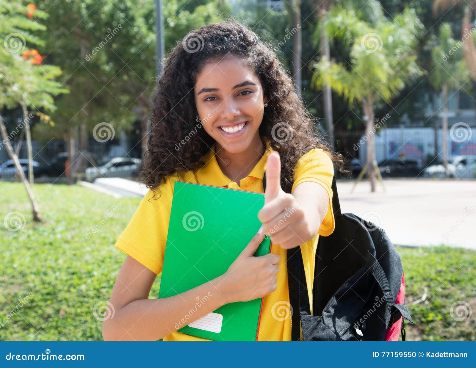 Étudiante latino-américaine avec de longs cheveux foncés montrant le pouce