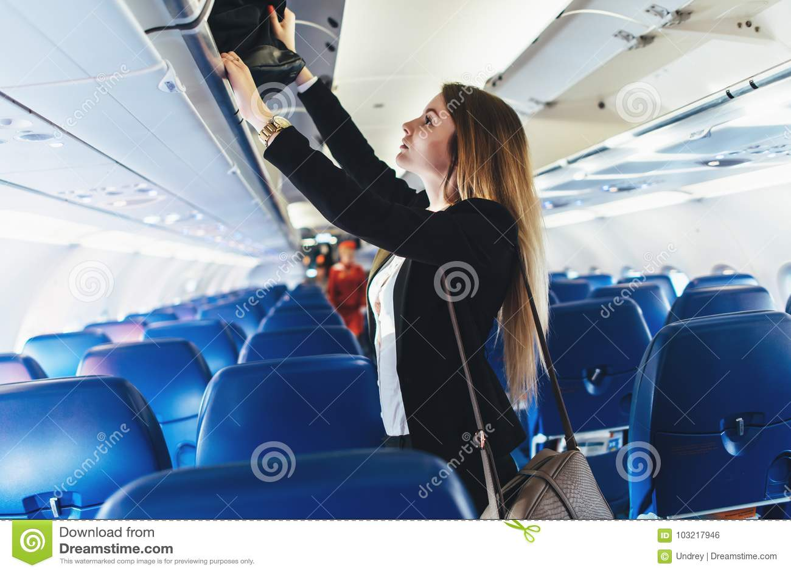 Étudiante mettant son bagage de main dans le casier aérien sur l avion