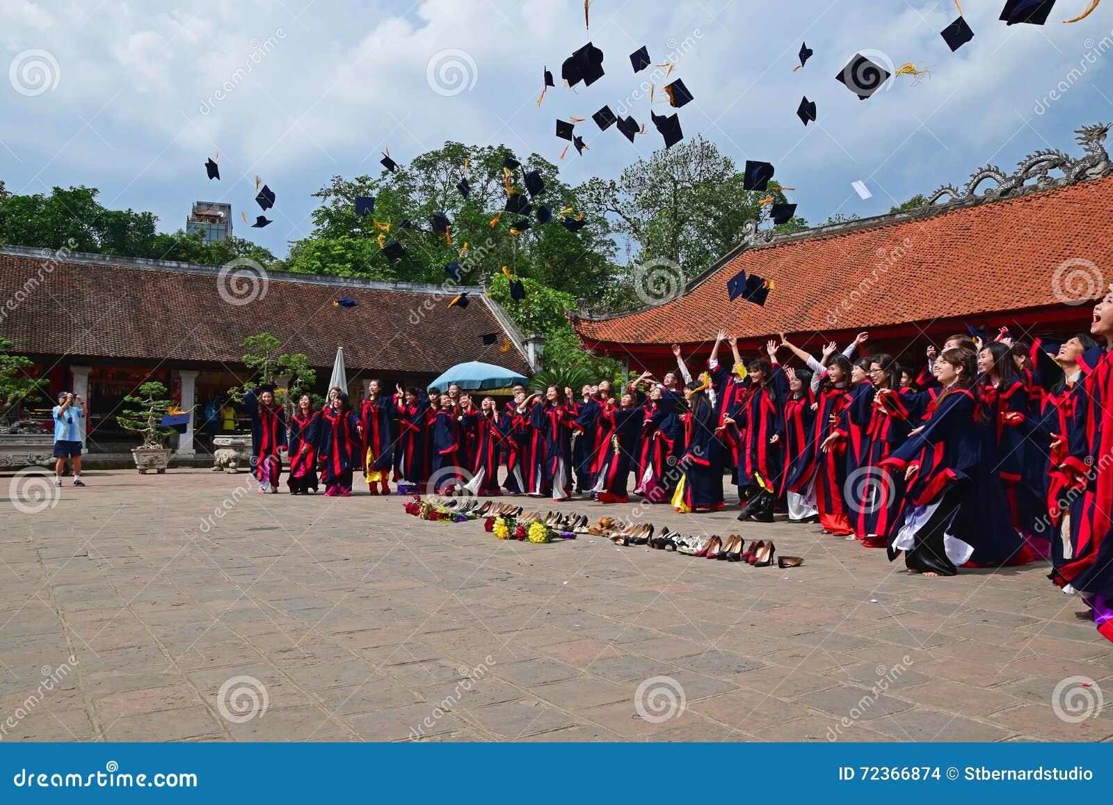 Étudiants ayant la cérémonie dans le temple de la littérature avec des chapeaux dans le ciel