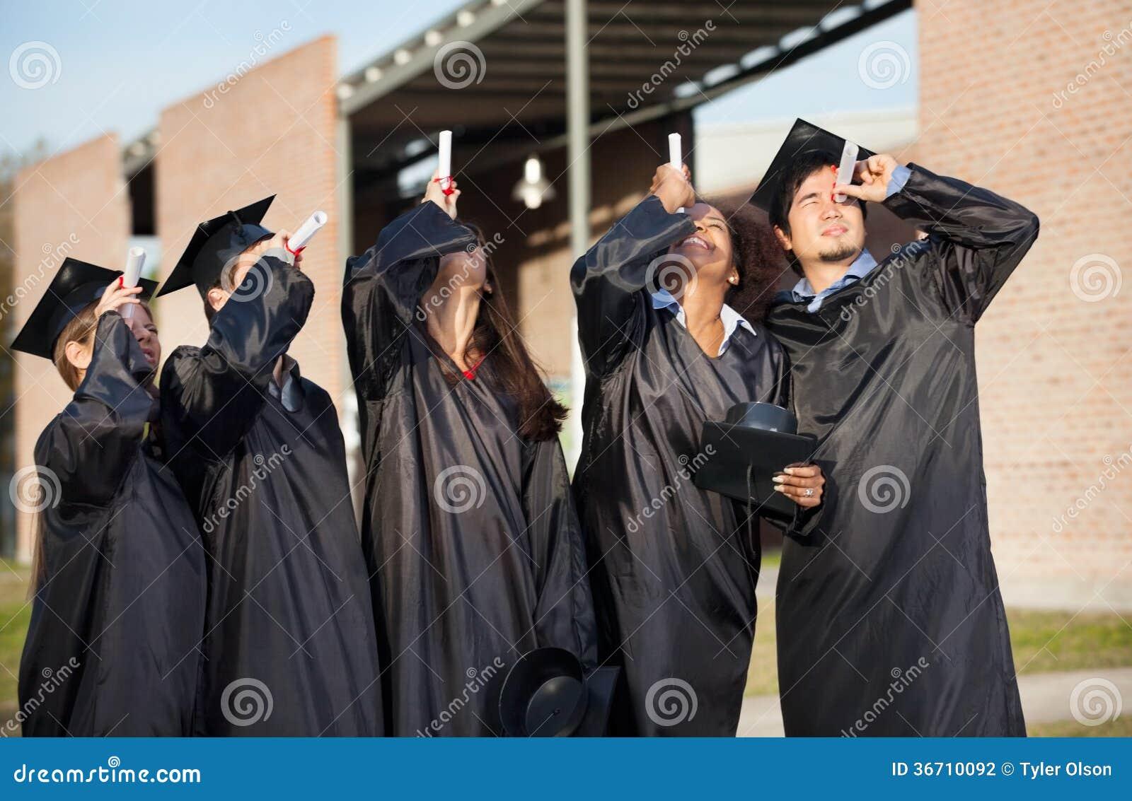 Étudiants dans la robe d obtention du diplôme regardant
