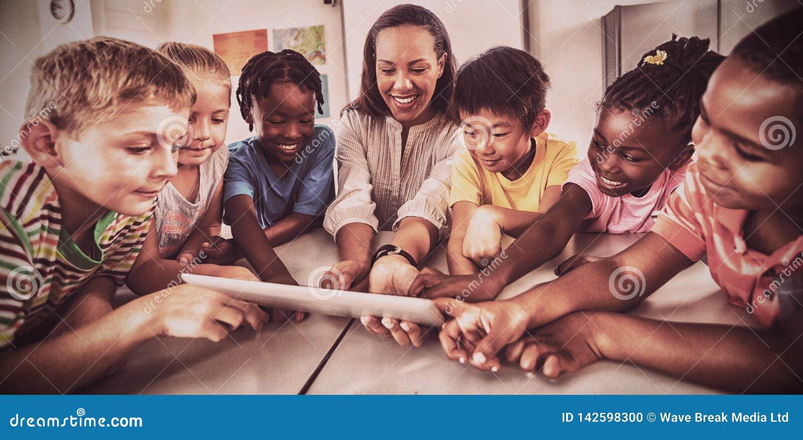 Étudiants et professeur de sourire à l aide d une tablette