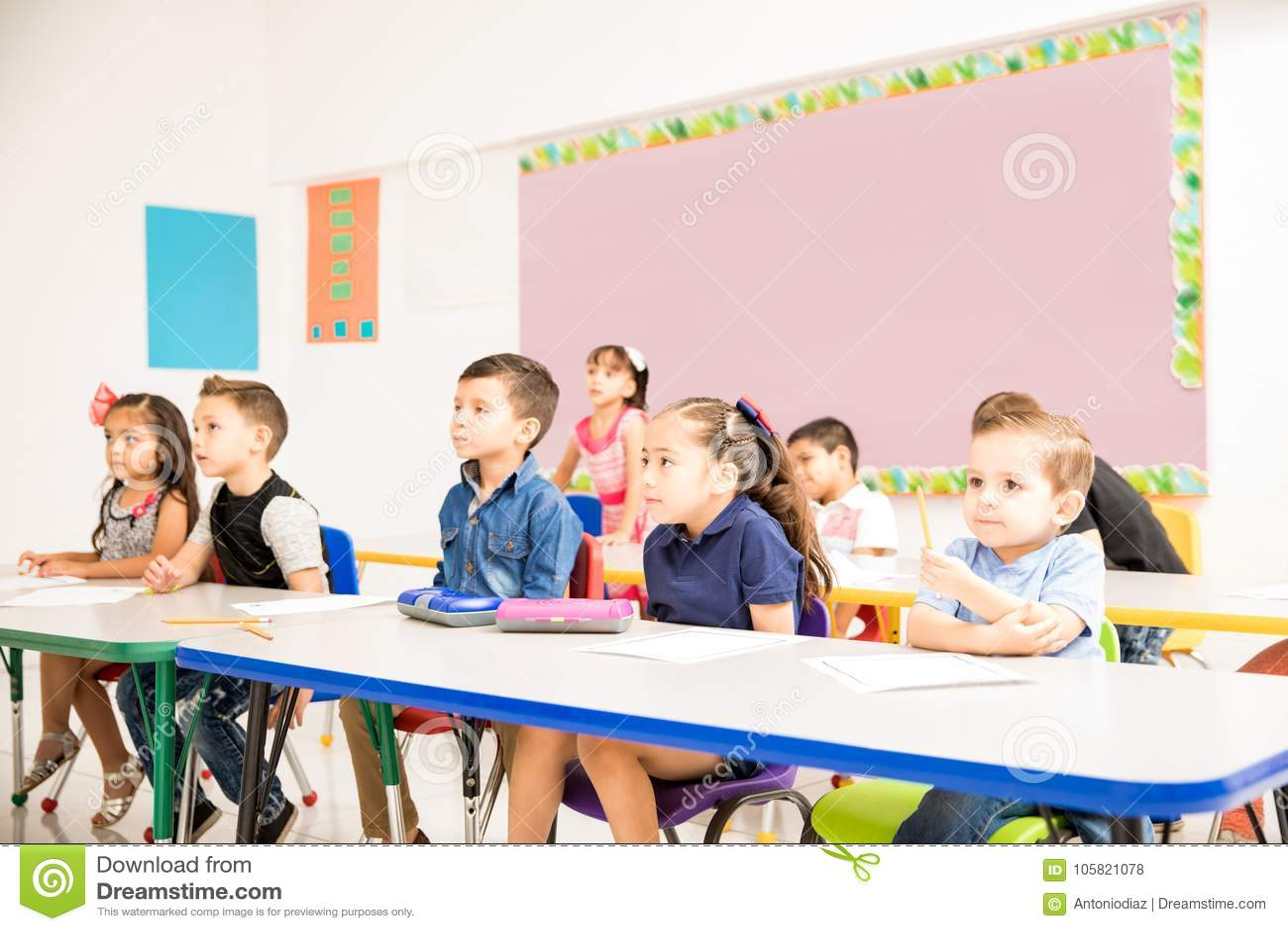 Étudiants préscolaires prêtant l attention à la classe