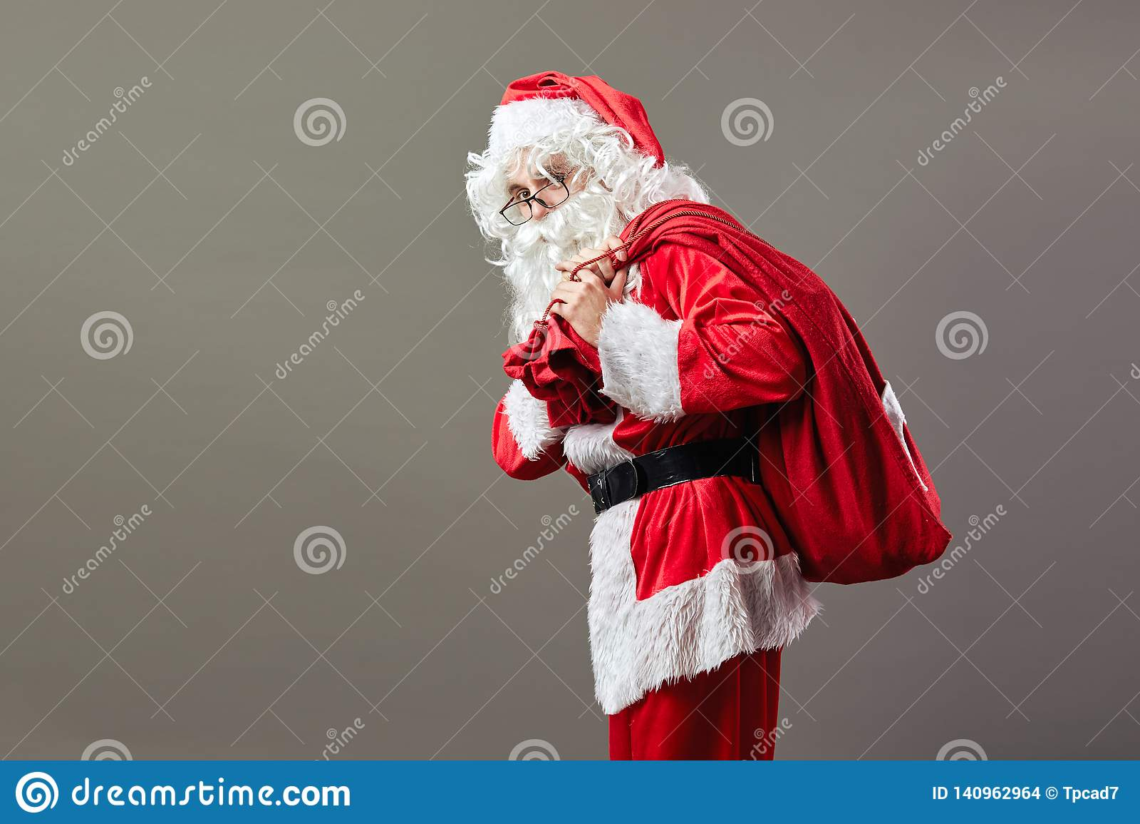 Άγιος Βασίλης στα γυαλιά στέκεται με την τσάντα με τα δώρα Χριστουγέννων στην πλάτη του στο γκρίζο υπόβαθρο