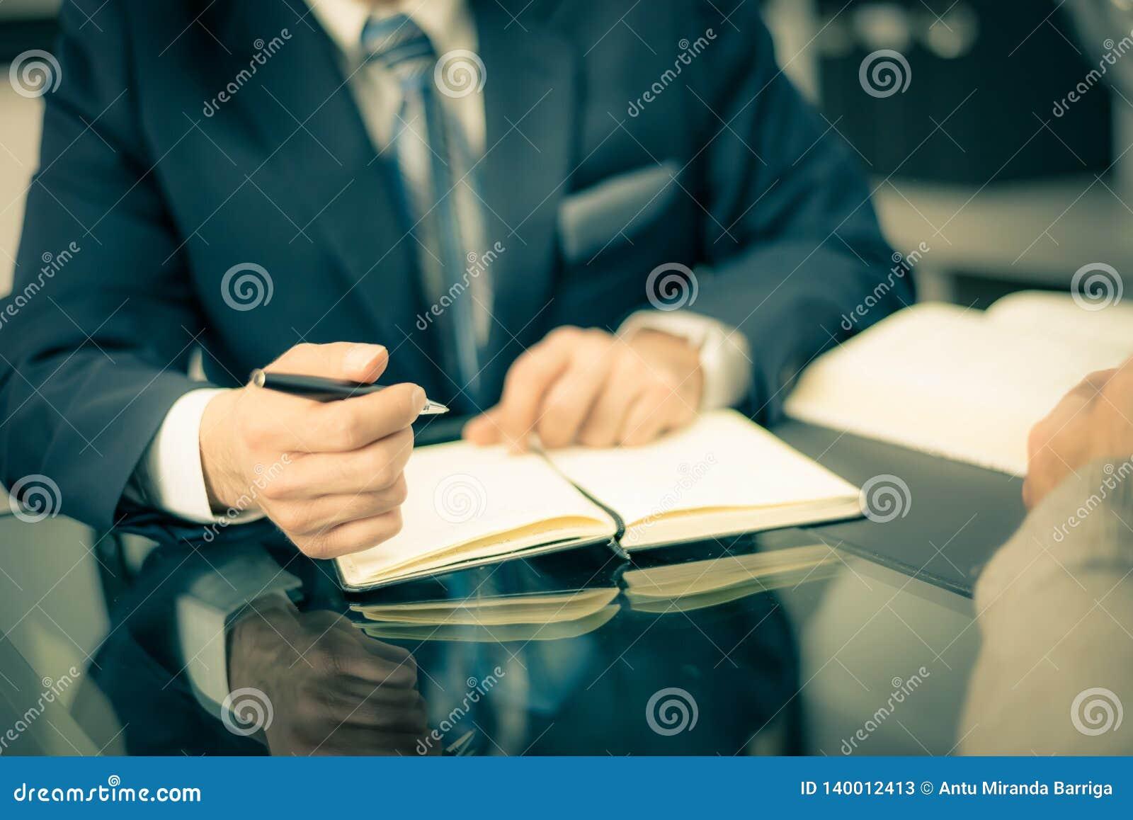 Άτομο σε ένα κοστούμι που κρατά μια μάνδρα και που παίρνει τις σημειώσεις