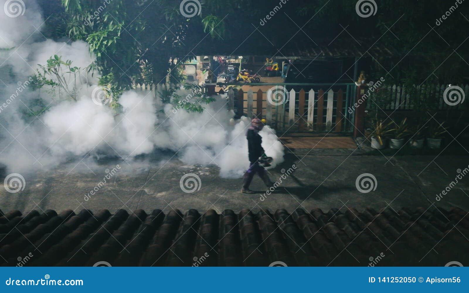 Άτομο που απελευθερώνει τον καπνό για να τακτοποιήσει τα κουνούπια και να προστατεύσει την ελονοσία στο χωριό τη νύχτα
