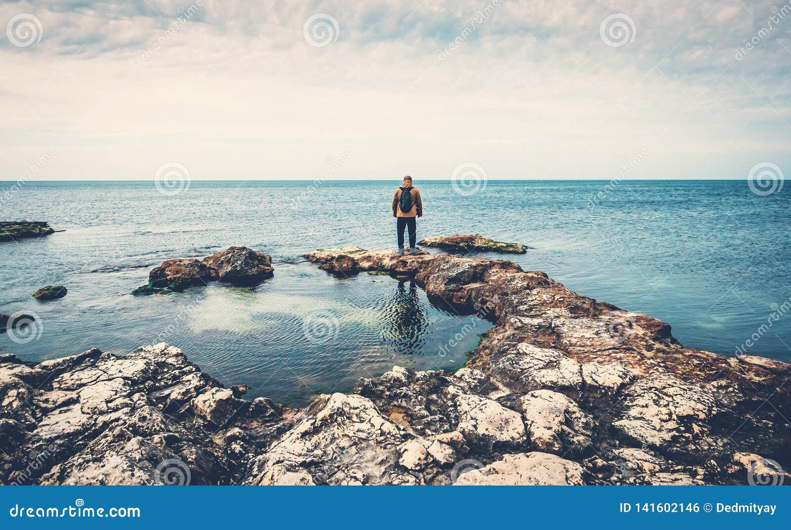 Άτομο που στέκεται στην εν πλω ακτή πετρών που εξετάζει τον ορίζοντα Παραλία, ωκεάνιες ταξίδι και έννοια ελευθερίας
