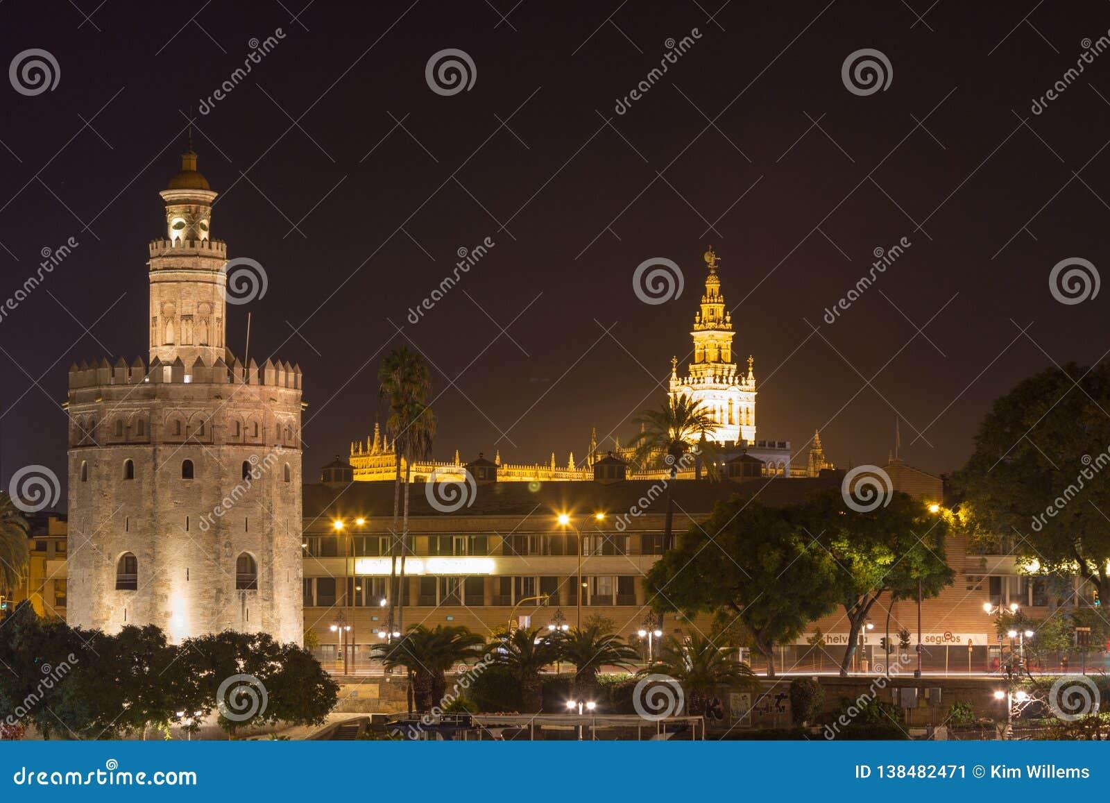 Άποψη σχετικά με Torre del Oro και Giralda από το calle Betis στη Σεβίλη τη νύχτα