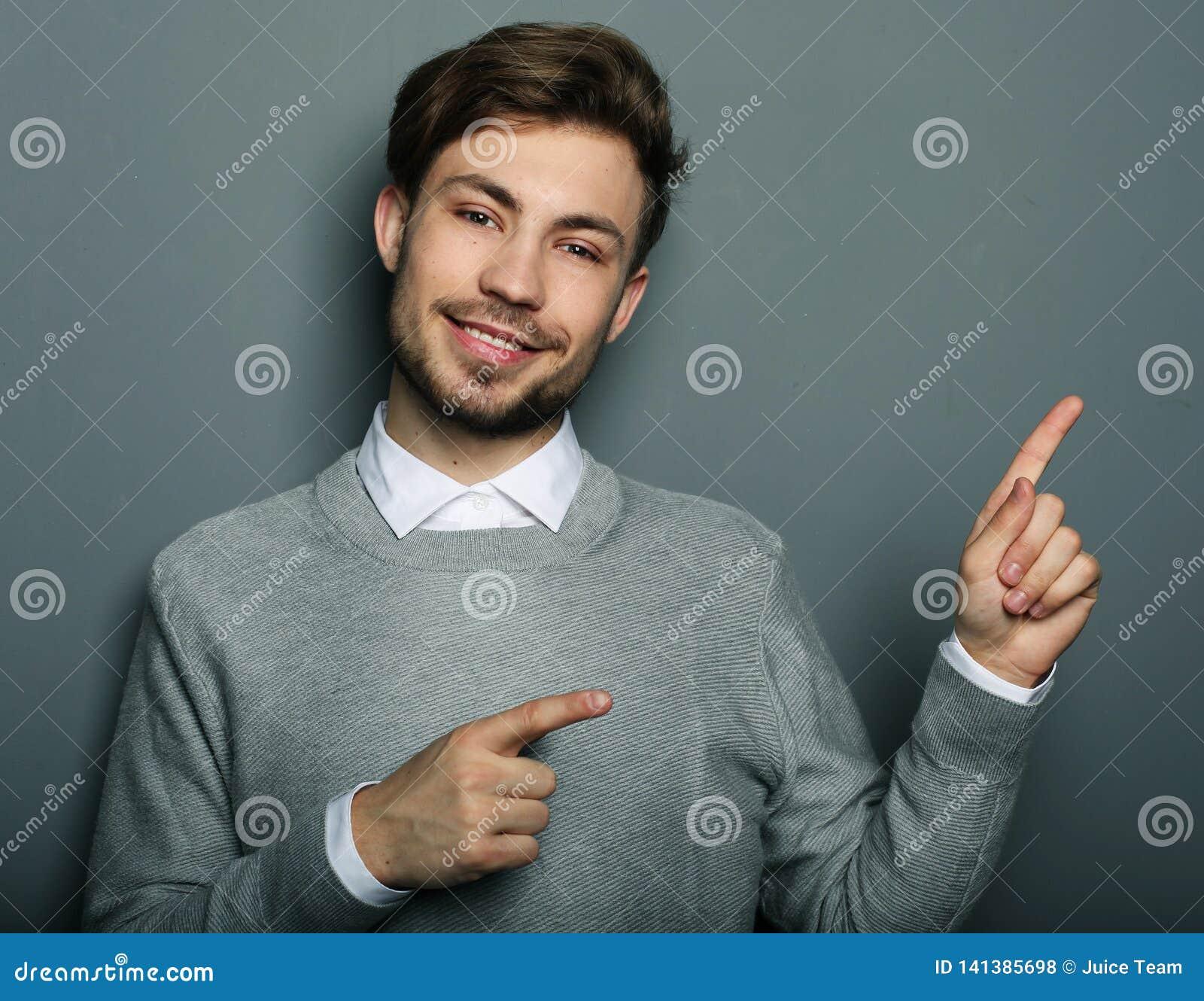 Ένας νέος και όμορφος επιχειρηματίας που δείχνει επάνω με το δάχτυλό του